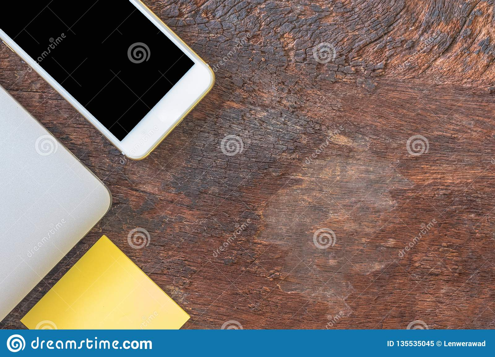 Top view smartphone, laptop, and post note or post it on old wooden background.