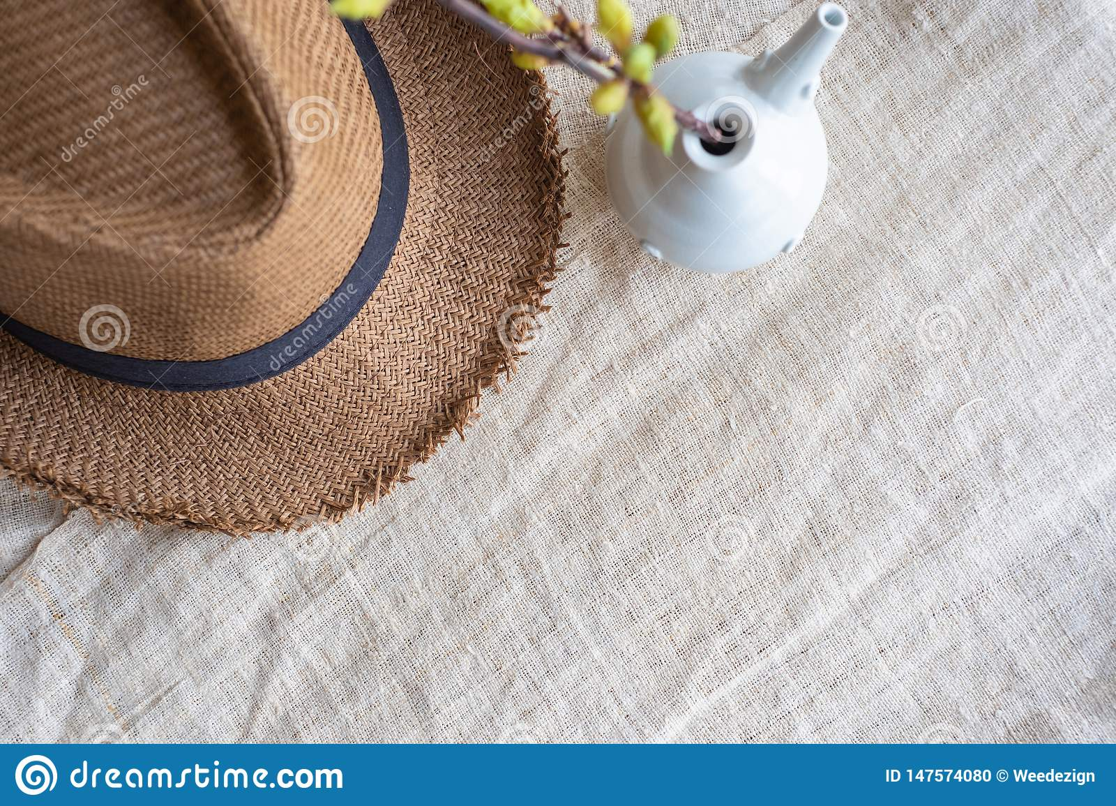 Top view of Summer brown panama straw hat with flower plant in vase on linen cloth.travel concept.copy space for adding text