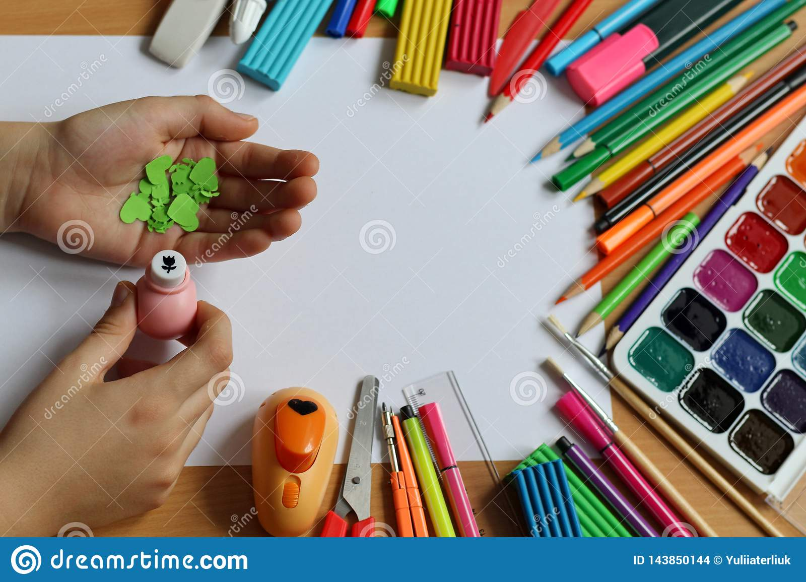 Top view of the table with a clean sheet of paper and a baby hands that make a gift. Mother`s Day and Women`s Day. Back to schoo