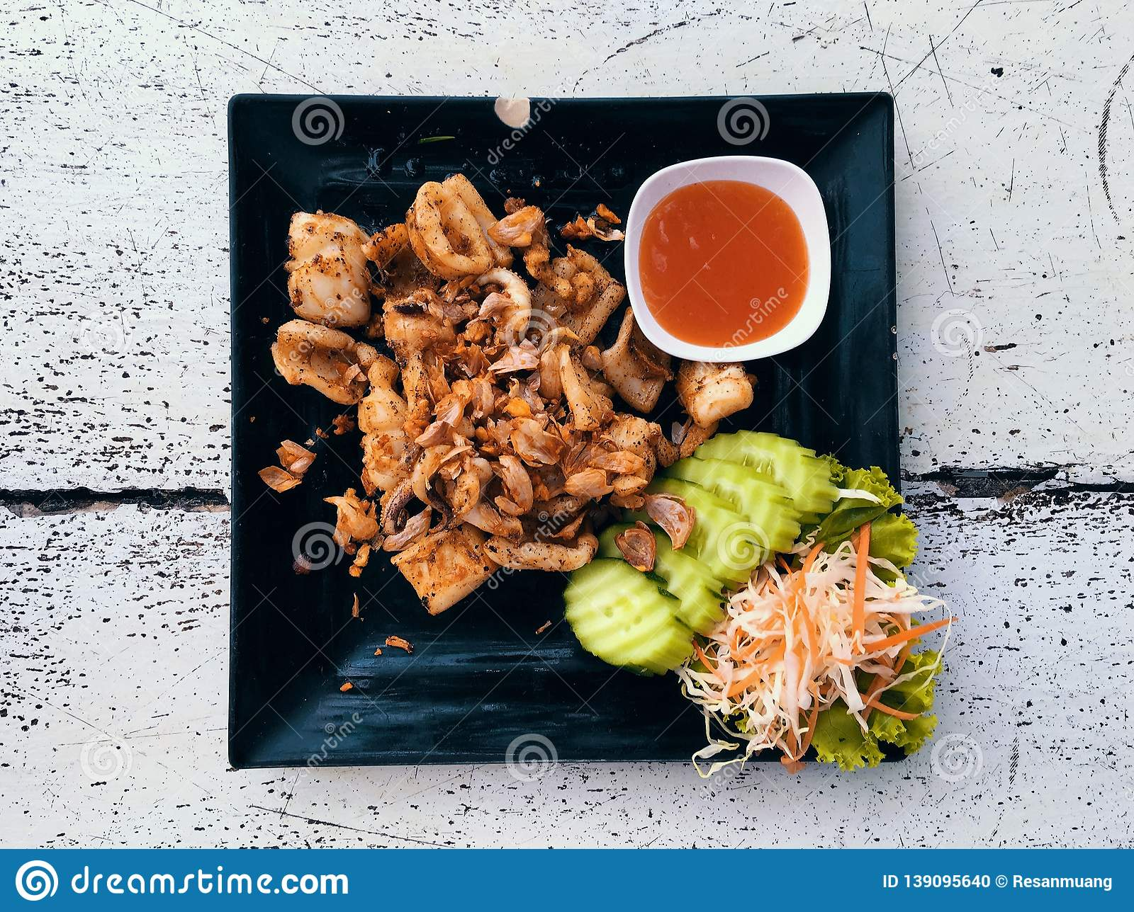 Top view Thai food fried squid in a black dish.