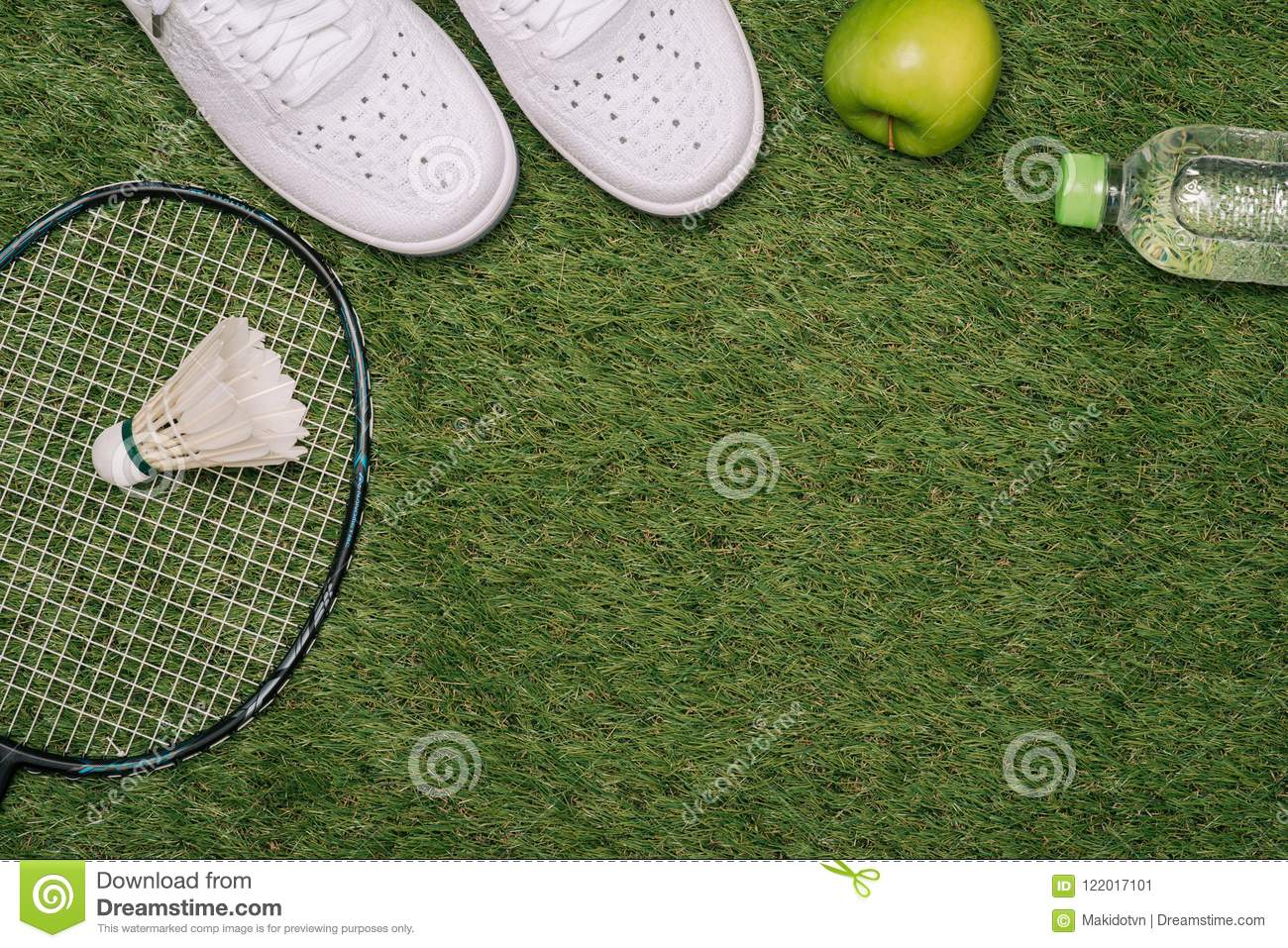 Top view of various sport equipment on green grass