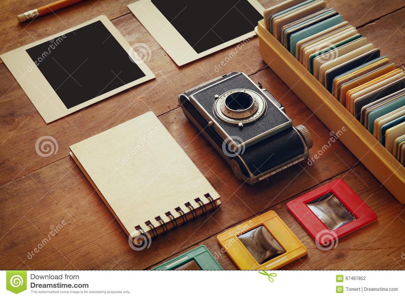 top view of vintage camera and old slides frames over wooden table