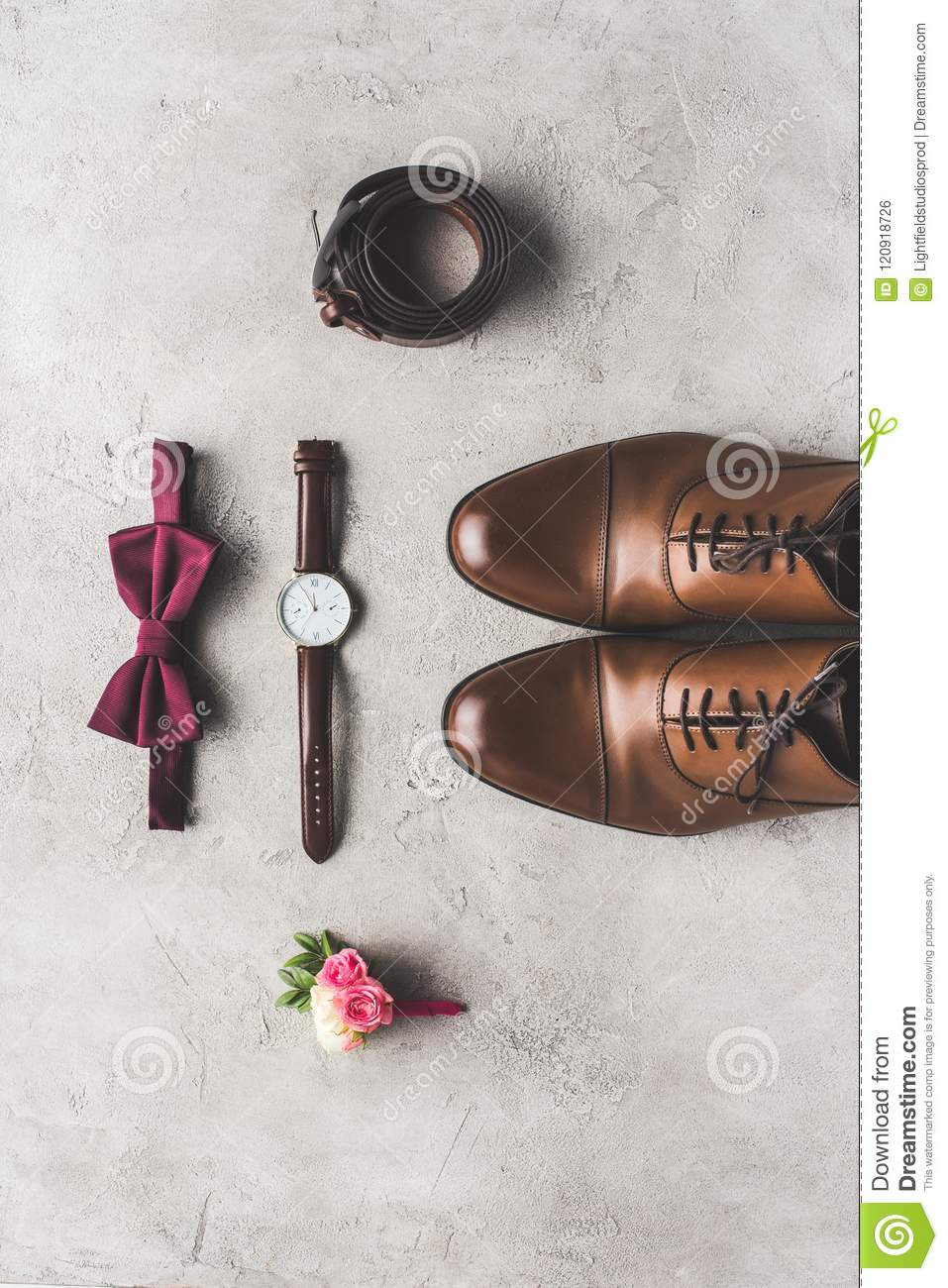top view of wedding bow tie, boutonniere, wristwatch and shoes for groom