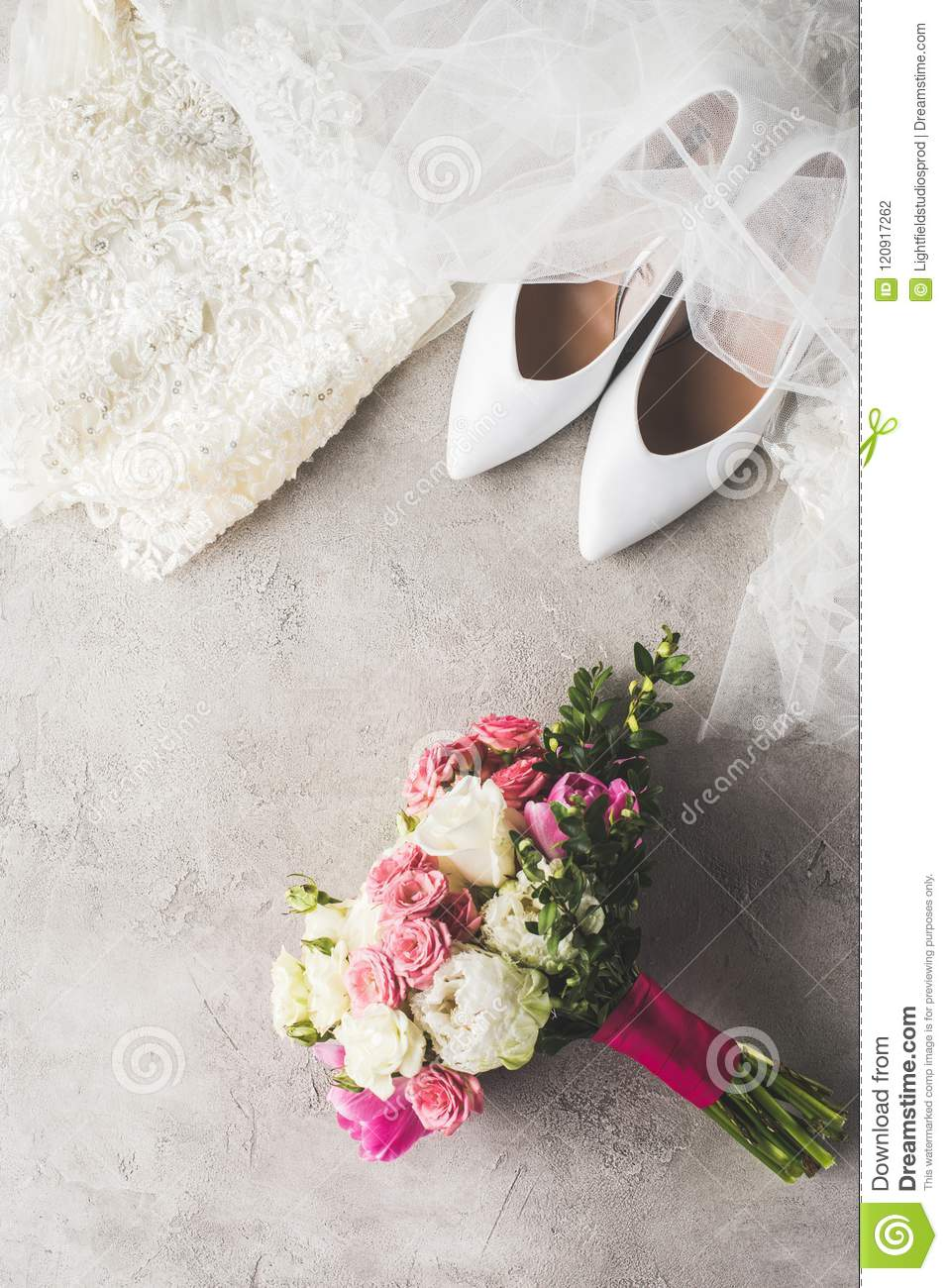 top view of wedding dress, shoes and bouquet