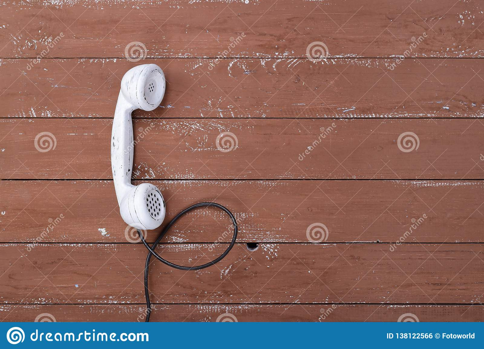 Top view white handset vintage phone on a brown wood textured