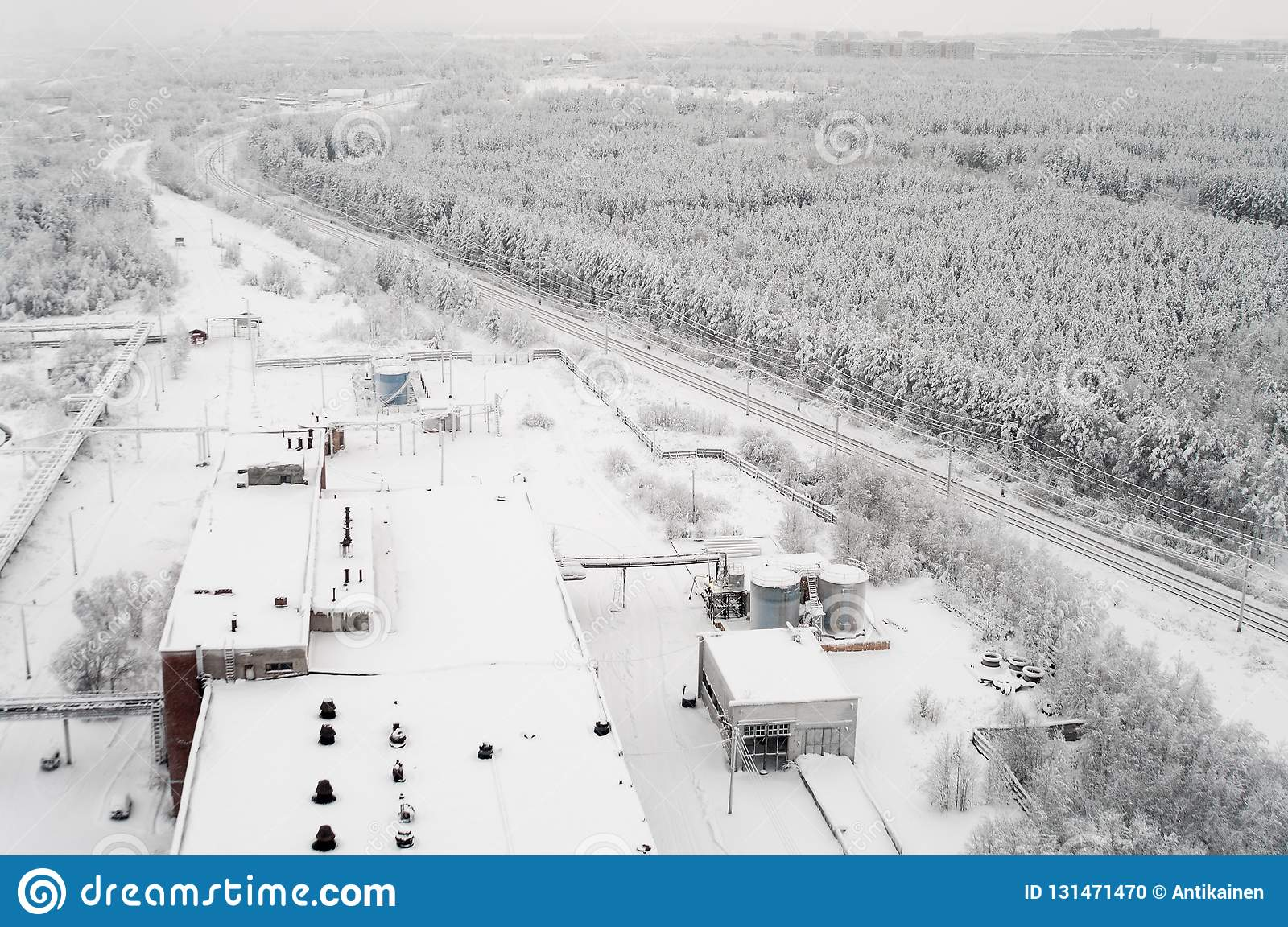 Top View At Wintry Rail Road In Evergreen Forest With Snow Capped