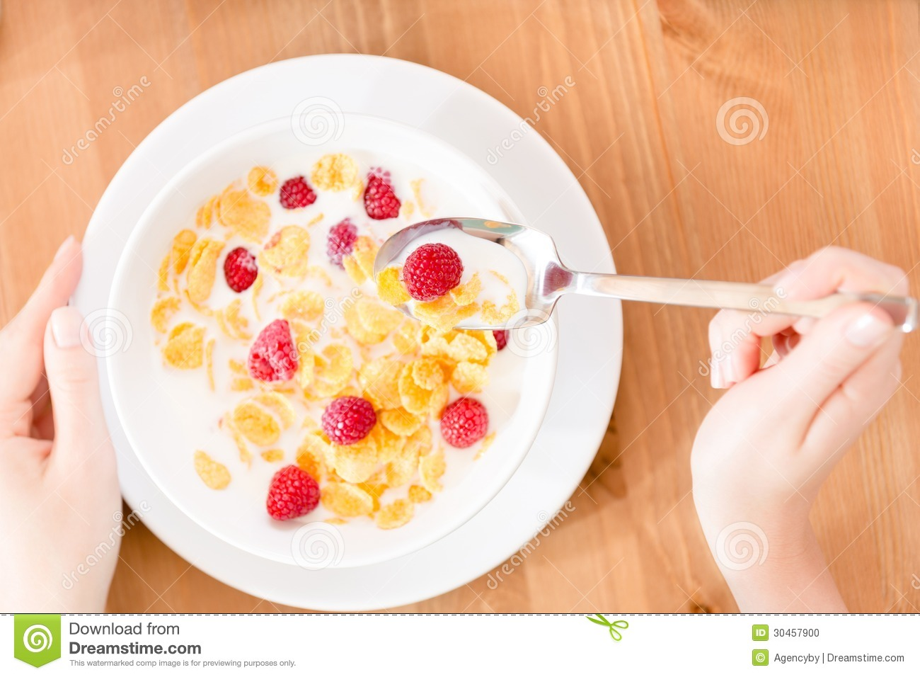 Top view of woman eating muesli with strawberry and milk