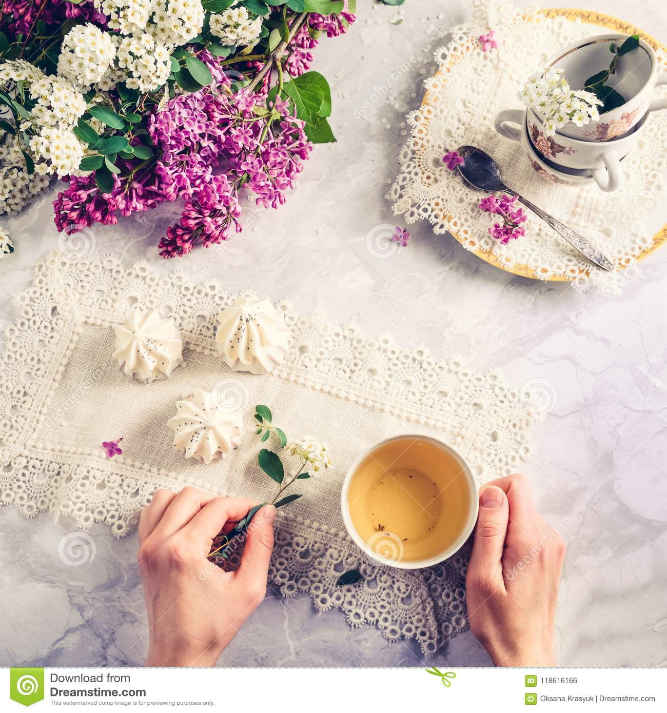 Top view woman`s hands holding vintage cup of green tea and spiraea branch on the table with meringue cakes, a bouquet of blossom