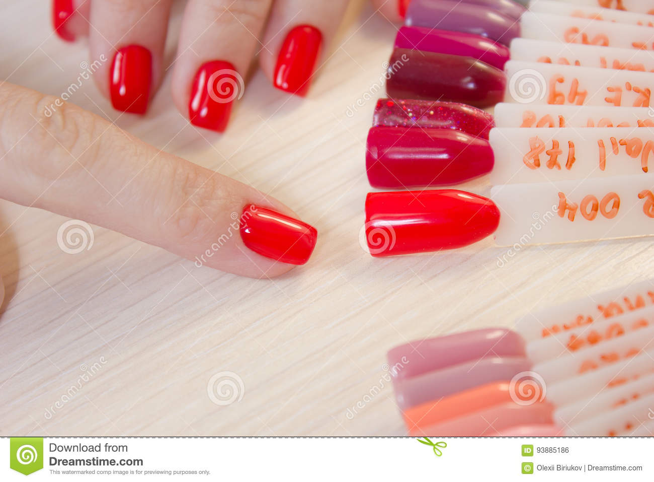 Top view woman selects yellow color shellac nail polish.Nail technician shows the color palette of nail services in