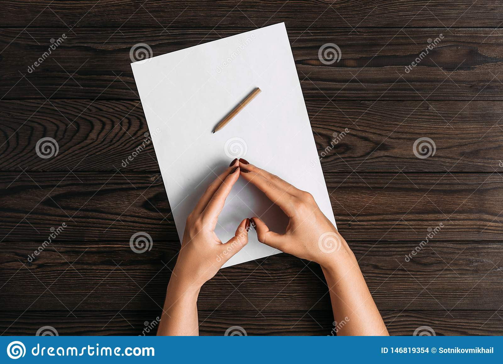 Top view of women`s hands, ready to write something on an empty piece of paper lying on a wooden table. White blank sheet of pape