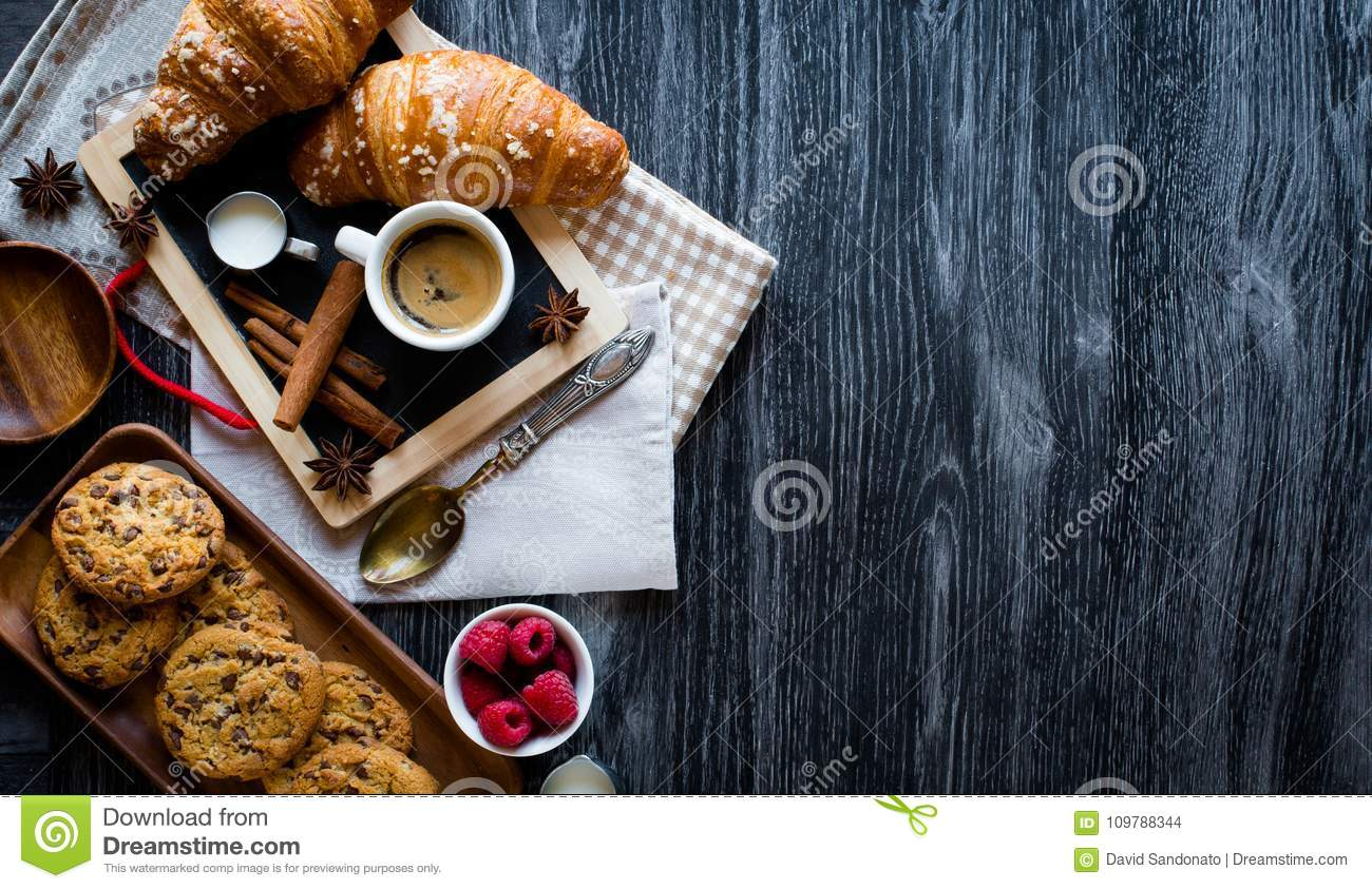 Top view of a wood table full of cakes, fruits, coffee, biscuits