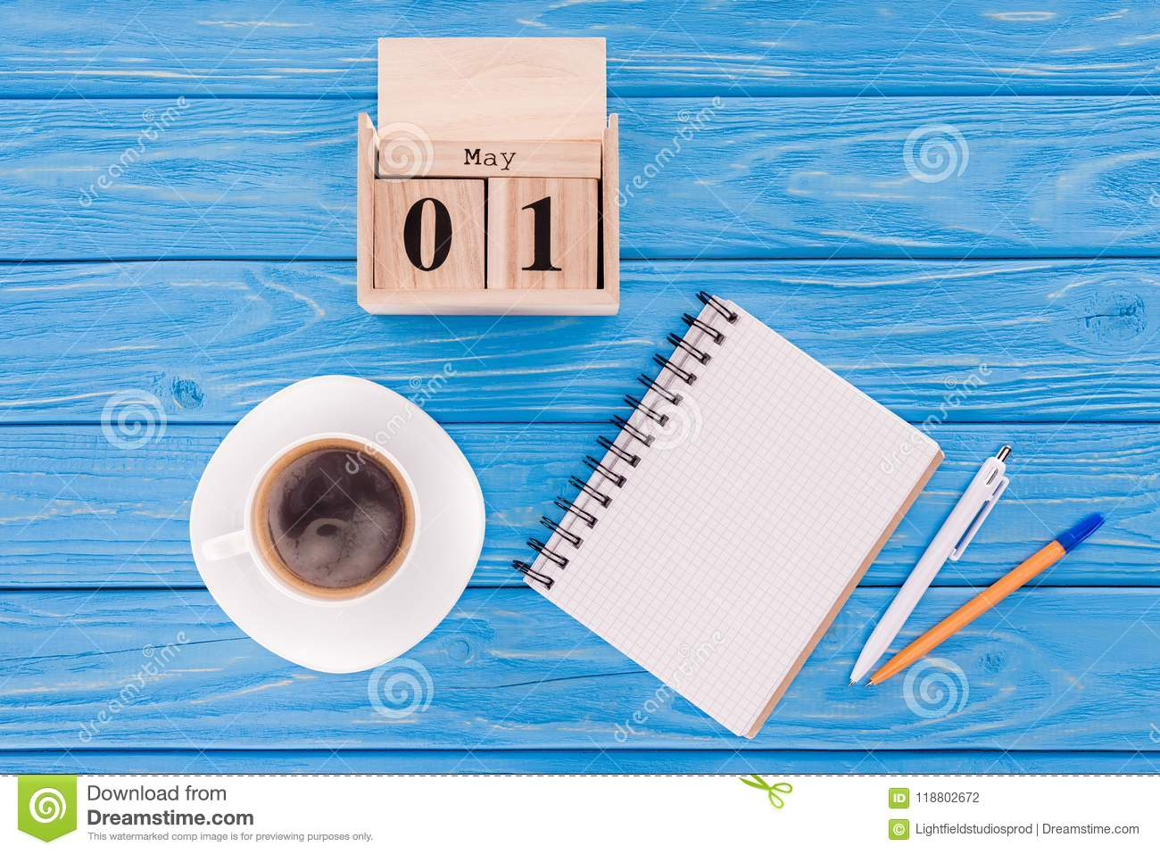 top view of wooden calendar with date of 1st may, coffee cup, blank textbook and pens, international workers day concept