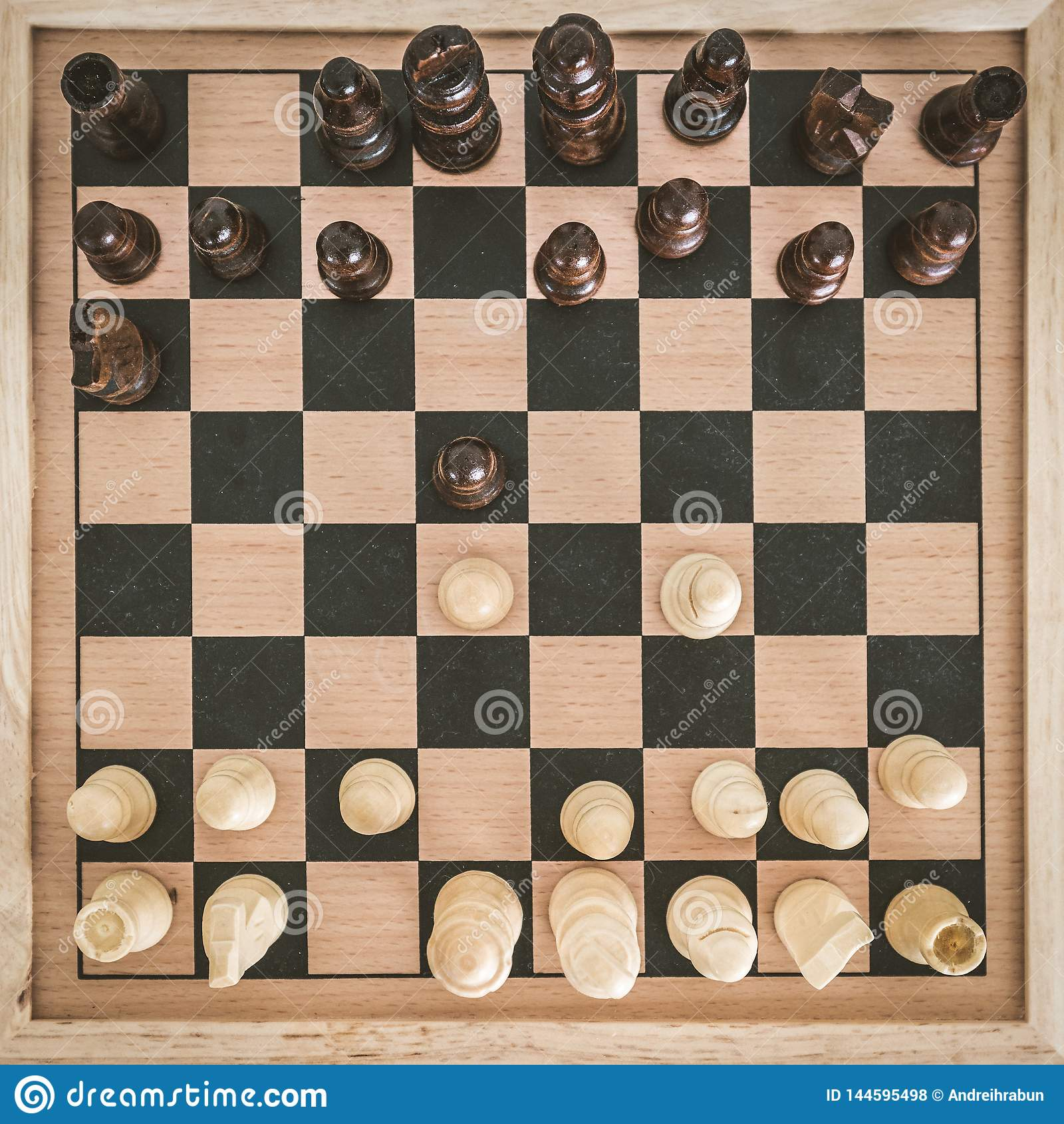 Top View On Wooden Chess Board With Chess Figures Ready For The Game And Man S Hand Making Chess Move On White Wooden Table Stock Photo Image Of White Strategy 144595498