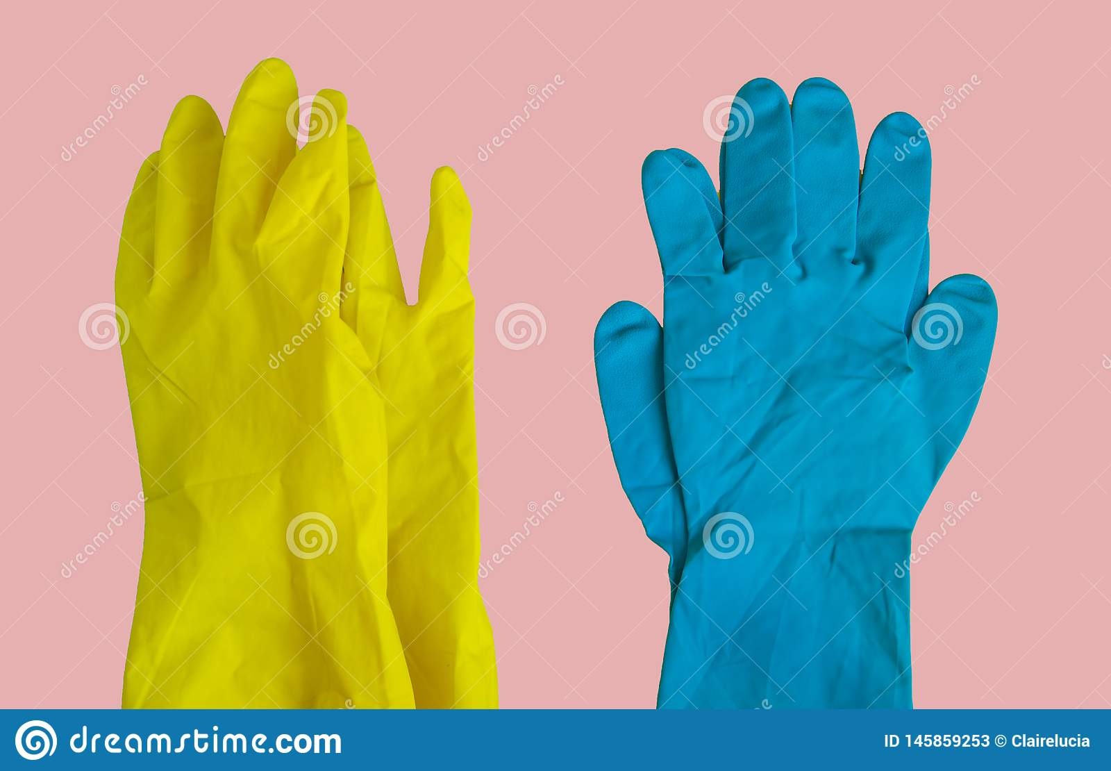 Top view of yellow and blue rubber protective gloves on pink table for spring or daily cleaning. The concept of a commercial