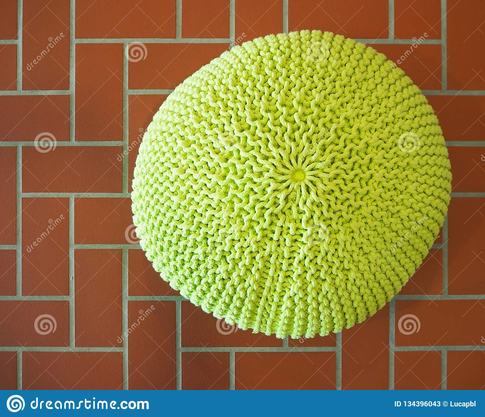Top view of a yellow wool pouf on terracotta tiles floor