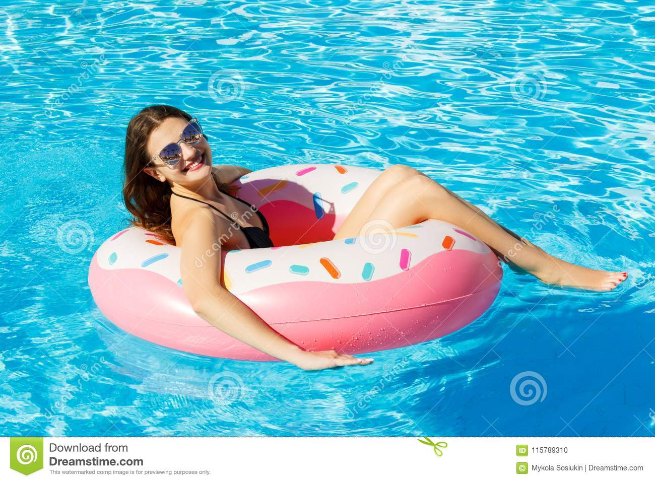 Top view of young female swim with pink circle in pool