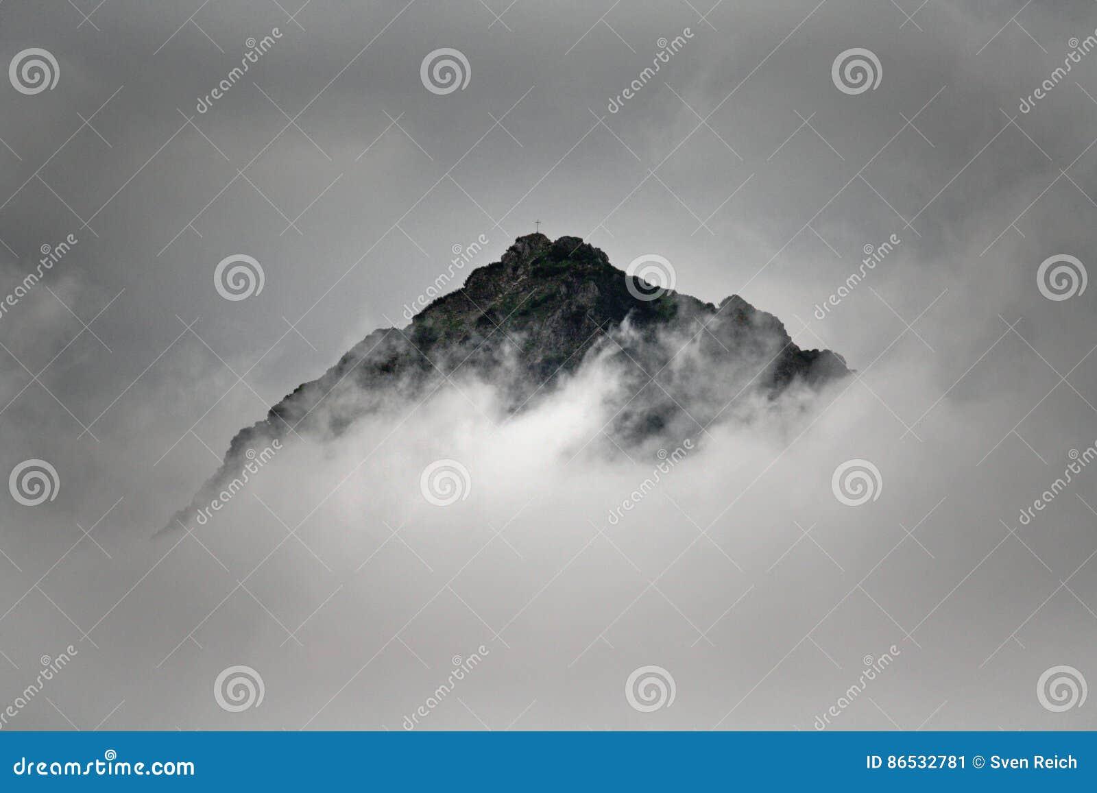 Toppmöte av ett berg i molnen