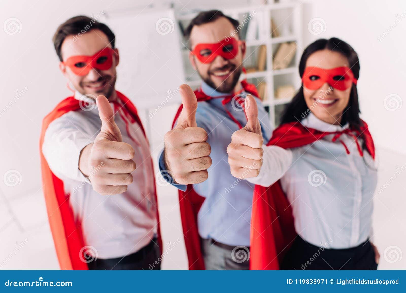 Toppna businesspeople i maskeringar och uddar som visar upp tummar