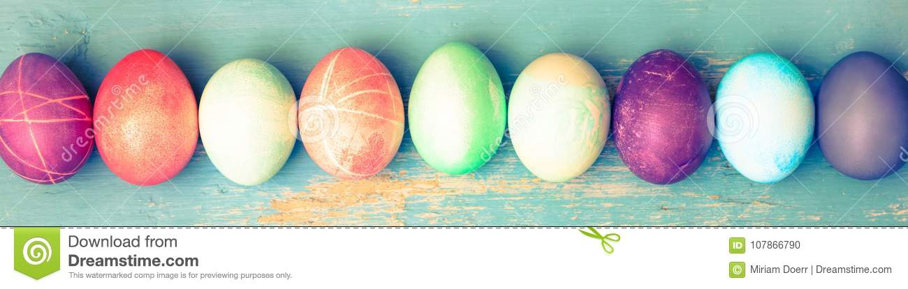 Topview, colorful dyed easter eggs on blue vintage wooden table