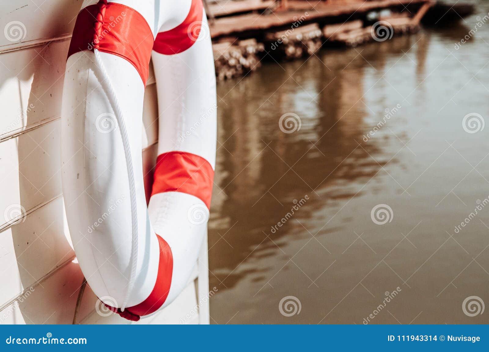 Tore rouge et blanc de balise de vie accrochant sur le mur en bois de la rivière la Floride
