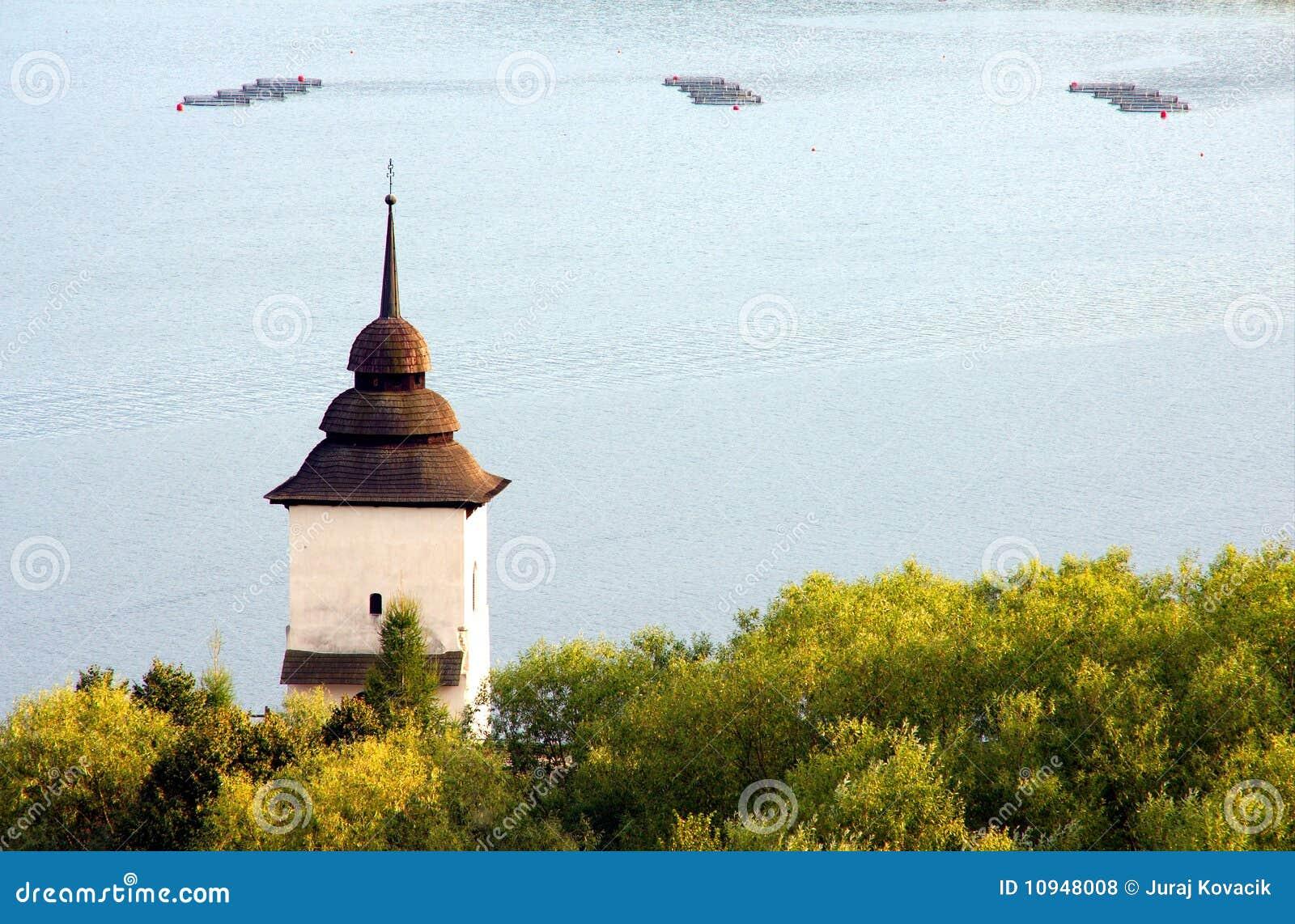 Toren van oude kerk door het meer