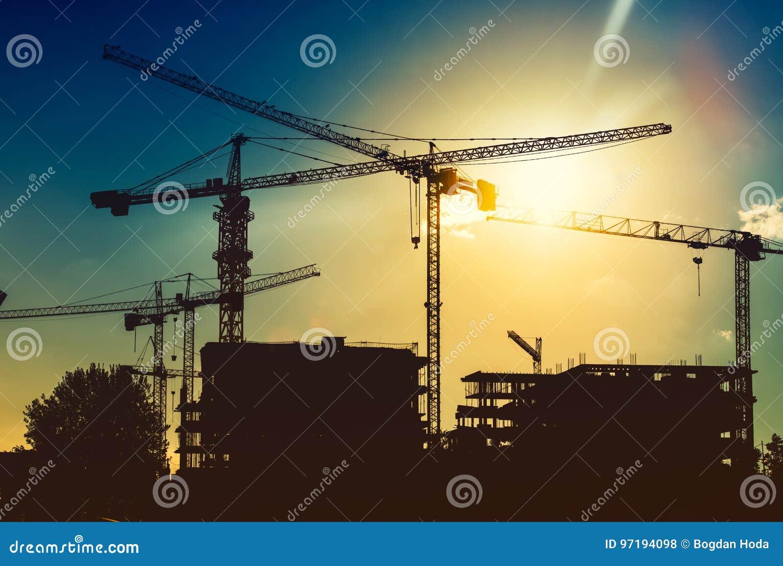 Torenkranen op industriële bouwwerf Nieuwe districtsontwikkeling en de wolkenkrabberbouw