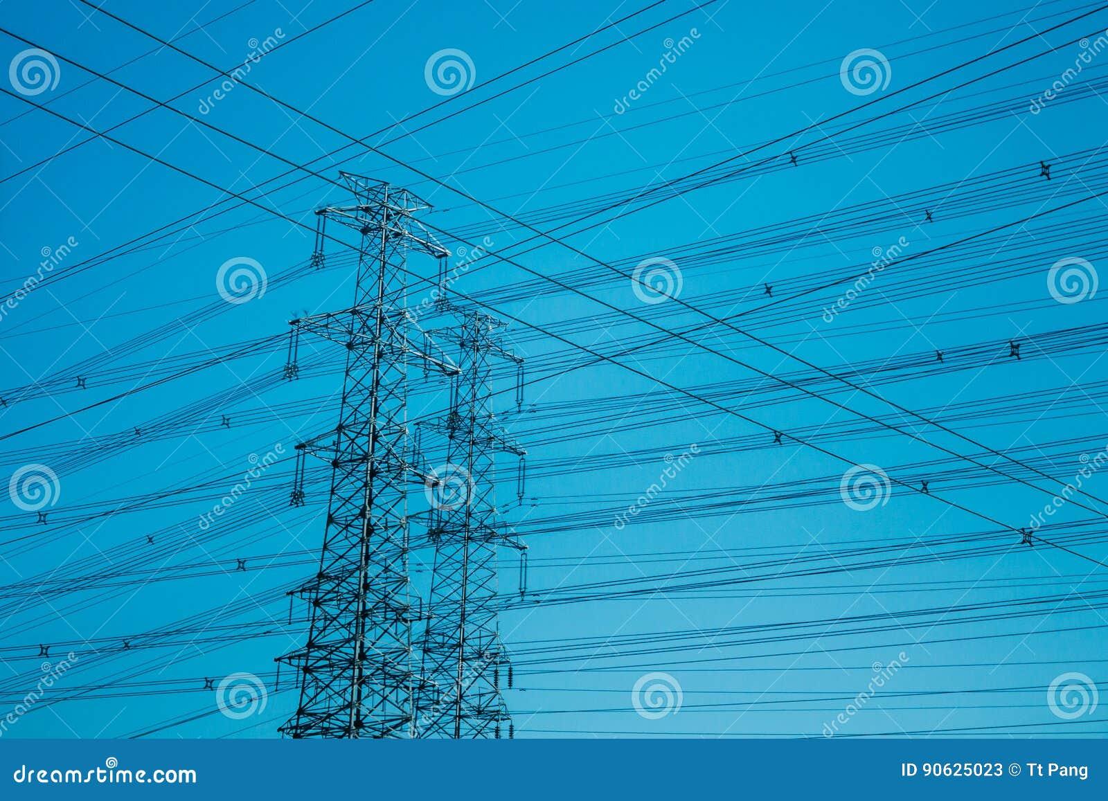Torens met hoog voltage die tegen blauw worden gesilhouetteerd