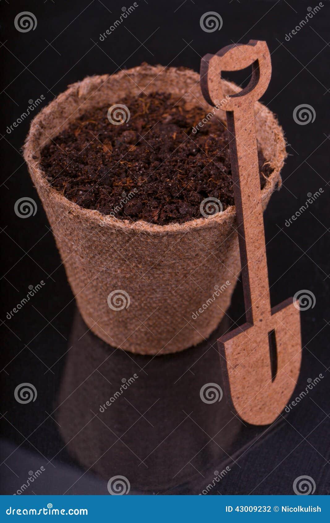 Torfowiskowy garnek z odżywki ziemią i dekoracyjną drewnianą łopatą