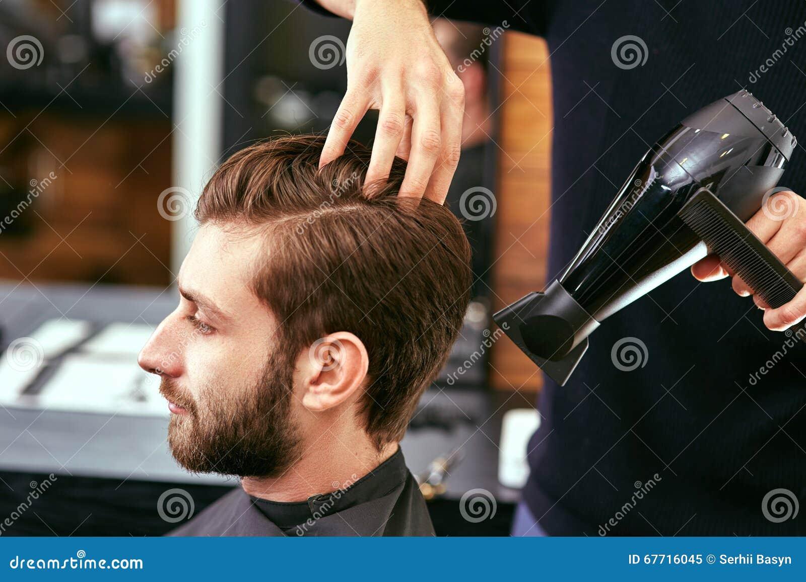 Torka som utformar mäns hår i en skönhetsalong