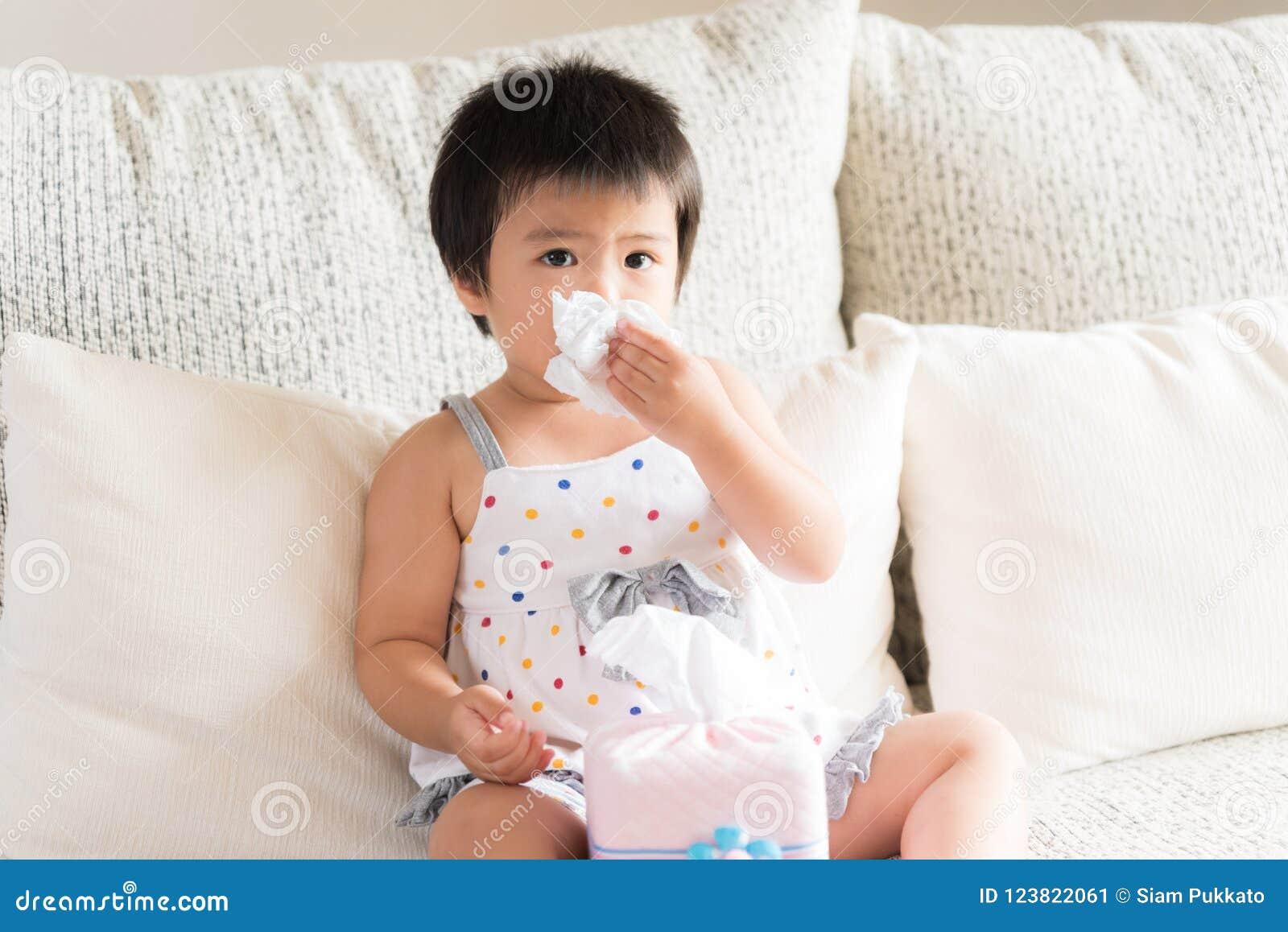 Torkande eller rengörande näsa för sjuk liten asiatisk flicka med tissu