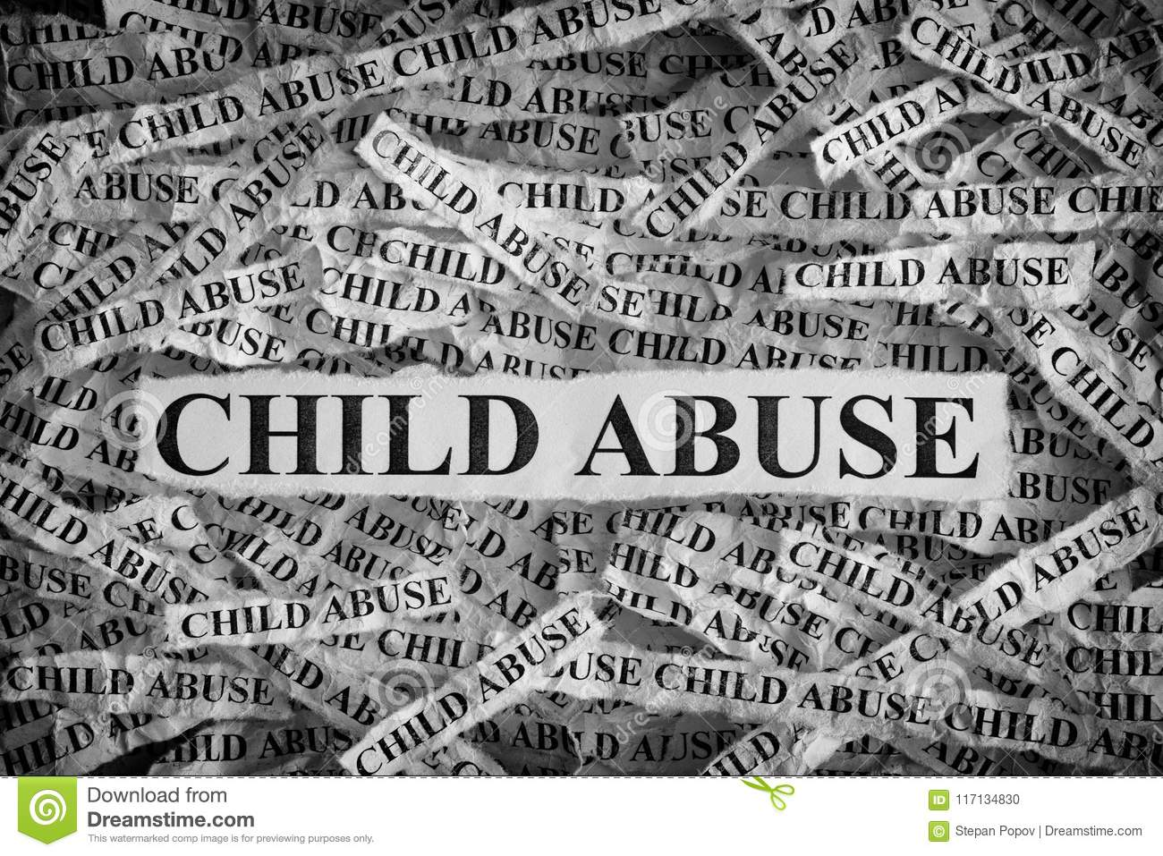 Torn pieces of paper with the words child abuse concept image black and white closeup
