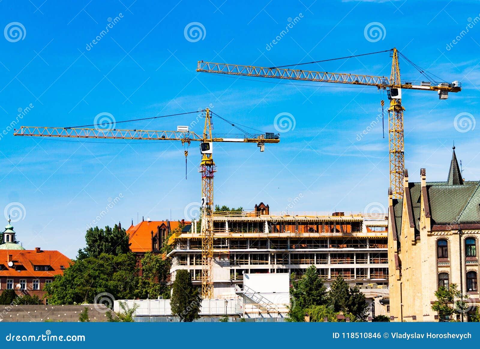 Tornkran, konstruktion av ett bostads- hus, en kran mot himlen, en motvikt, industriell horisont
