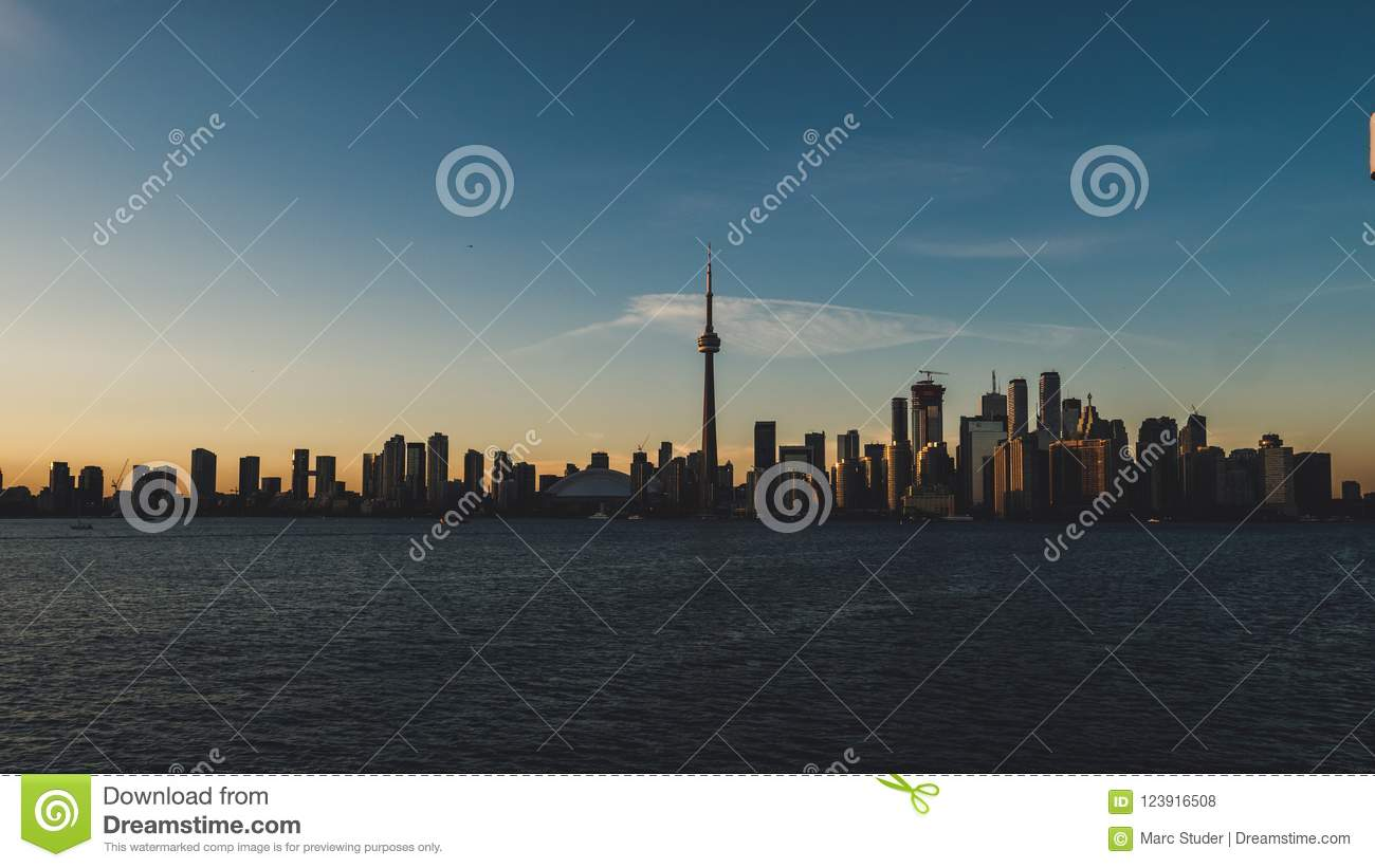 Toronto skyline during sunset seen from toronto island with lake ontario infront