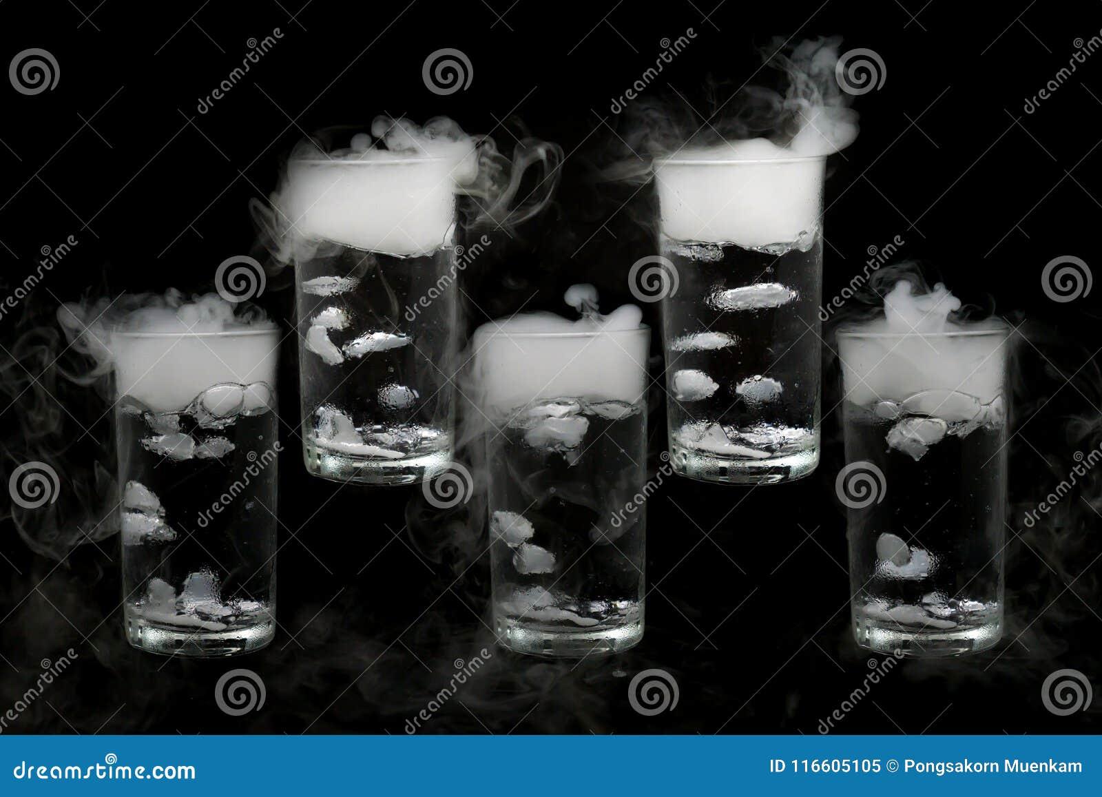 Torr is fem i ett exponeringsglas av vatten som isoleras på svart bakgrund rök slut upp