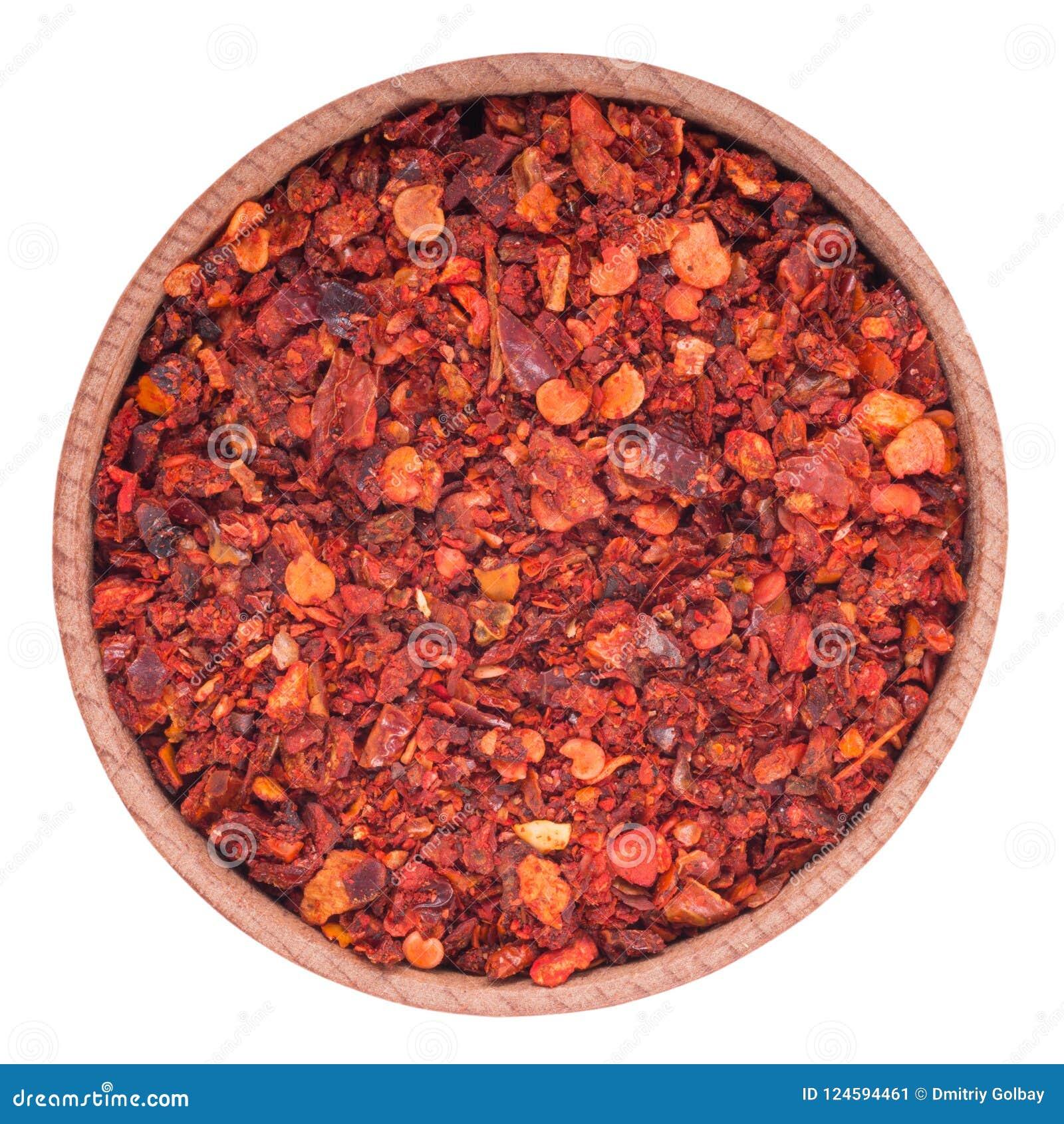 Torr paprika i en träbunke bakgrund isolerad white