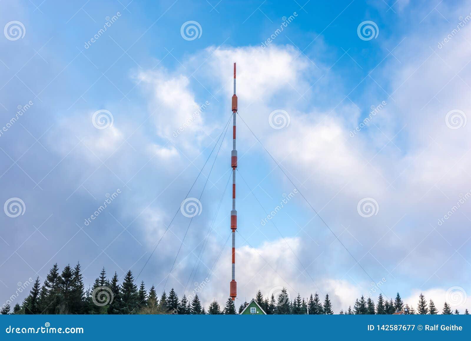 Torre alta mesma da transmissão na frente do céu azul nebuloso