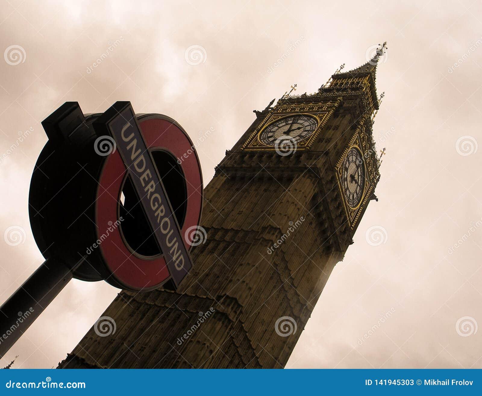 Torre de Big Ben y la muestra del metro de Londres contra un cielo nublado