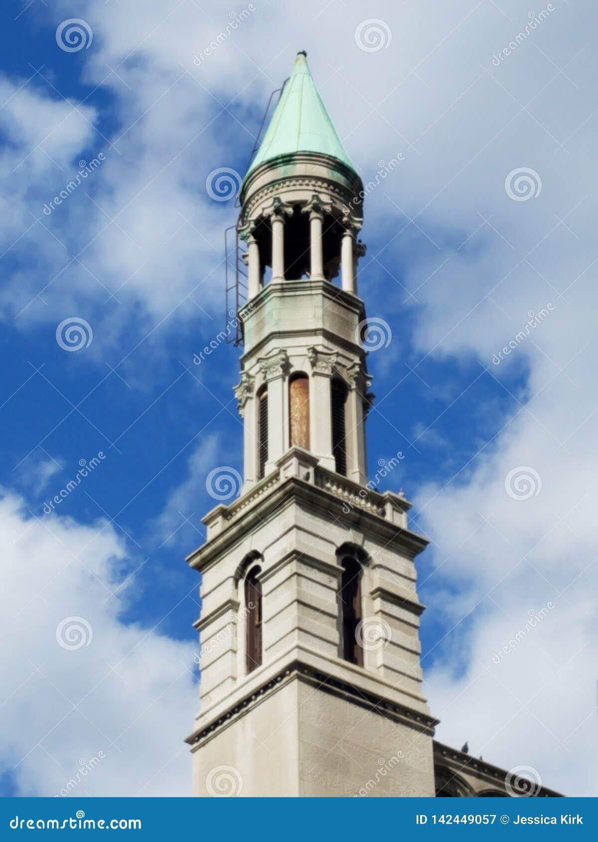 Torre de igreja e c?u azul com nuvens brancas