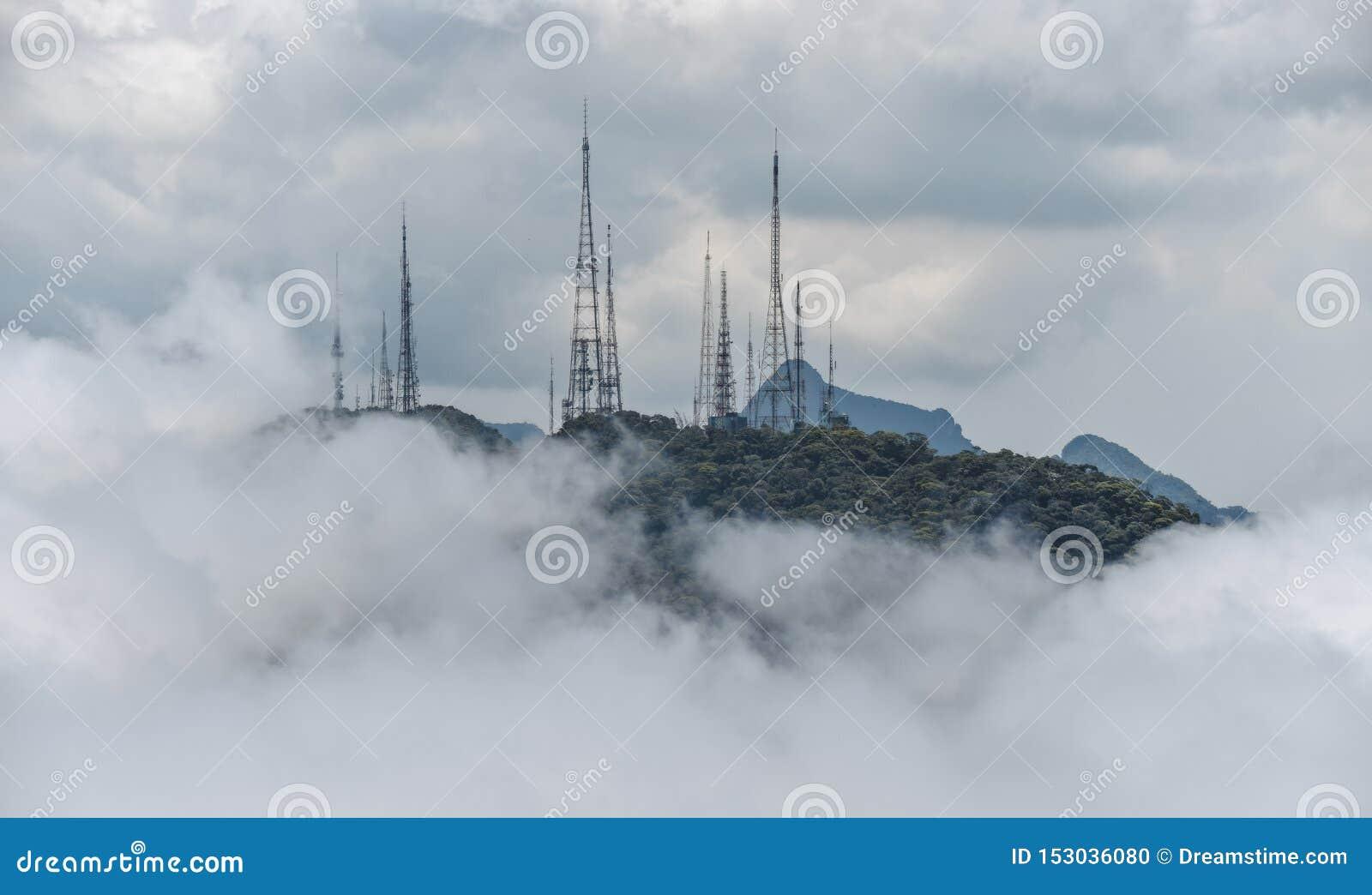 Torre de la transmisión de poder en la niebla en las montañas