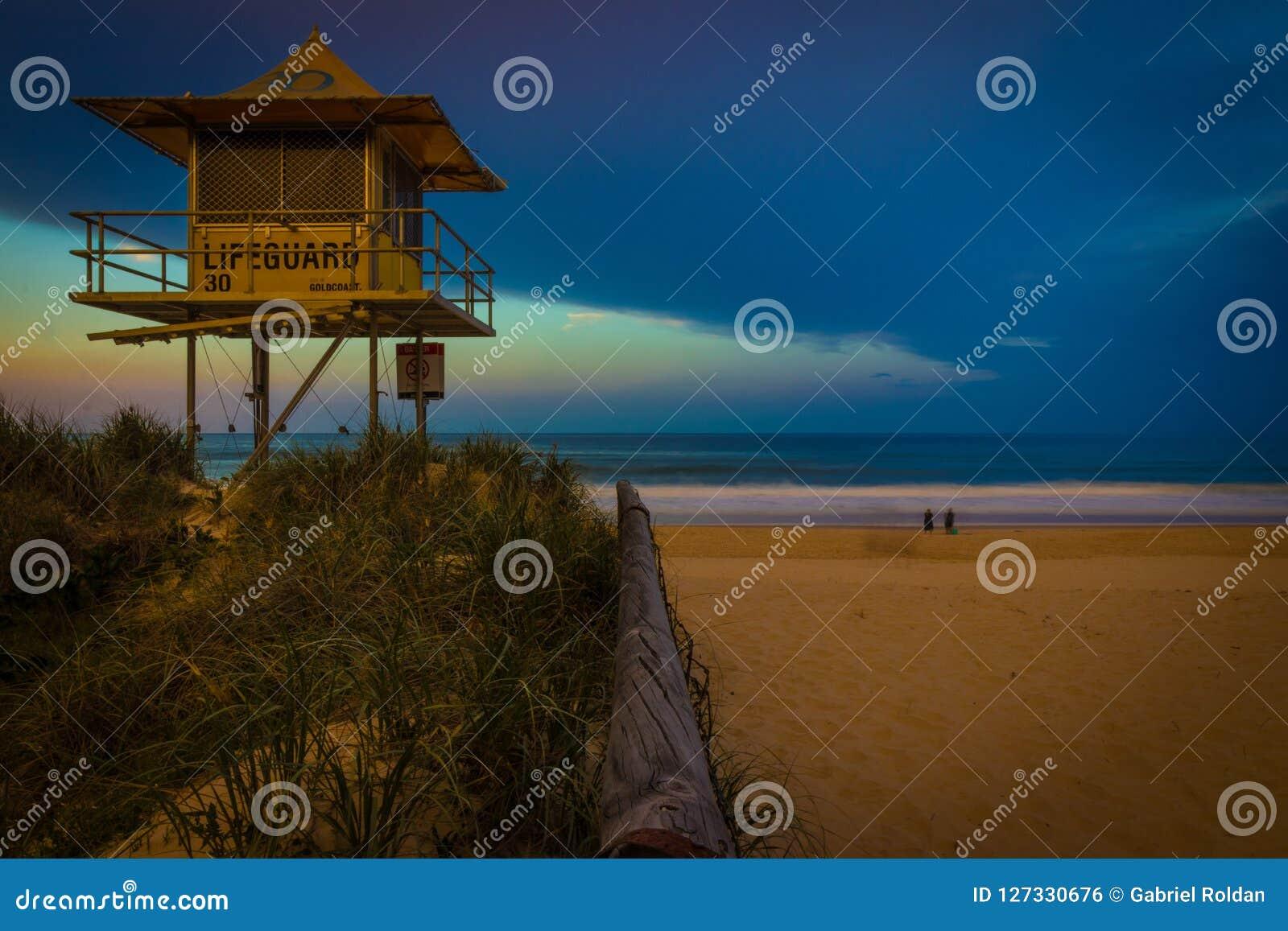 Torre del bagnino in erba vicino alla spiaggia di sabbia, al mare ed agli esseri umani