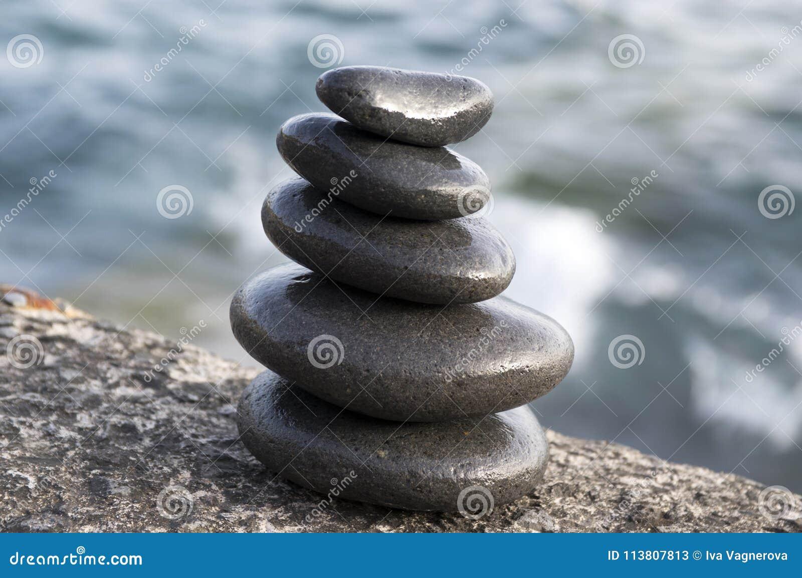 Torre del cairn di cinque pietre, scultura di zen della roccia, ciottoli neri e fondo blu-chiaro dell oceano