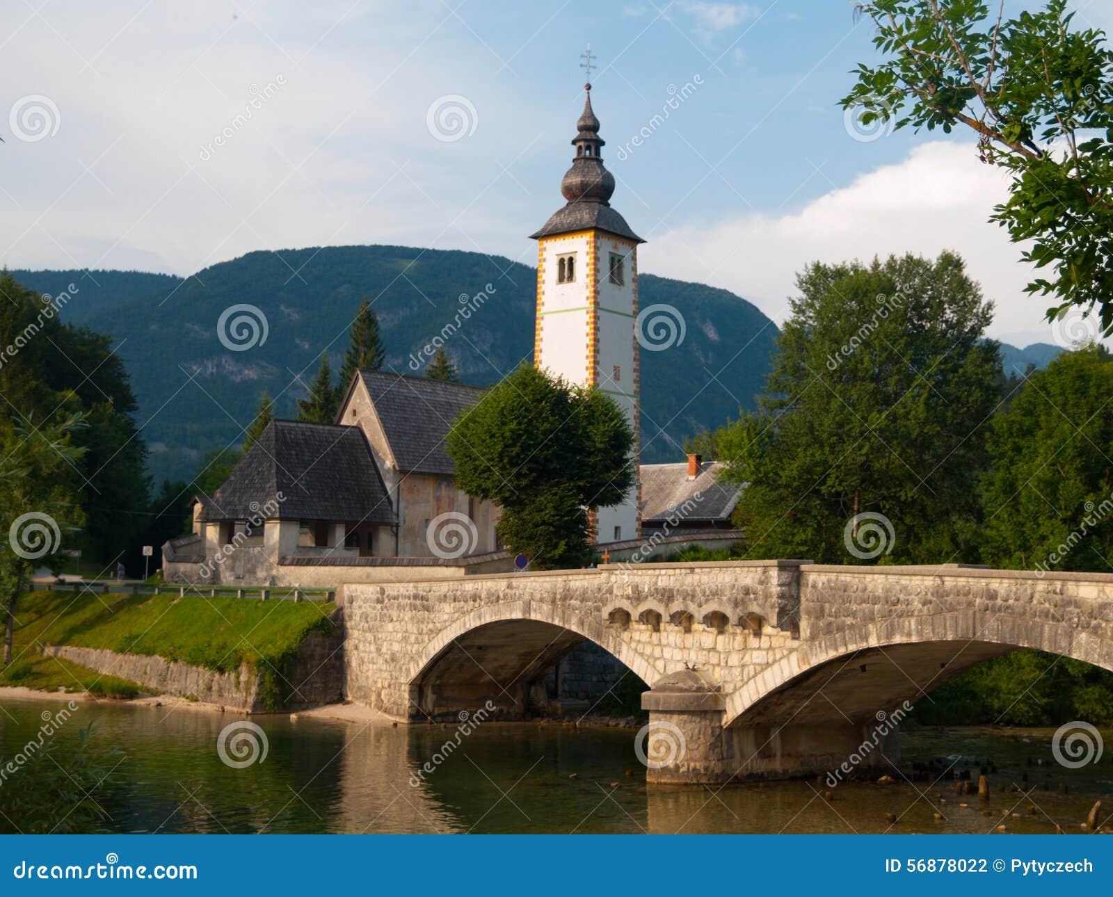 Torre di chiesa e ponte della pietra nel lago Bohinj