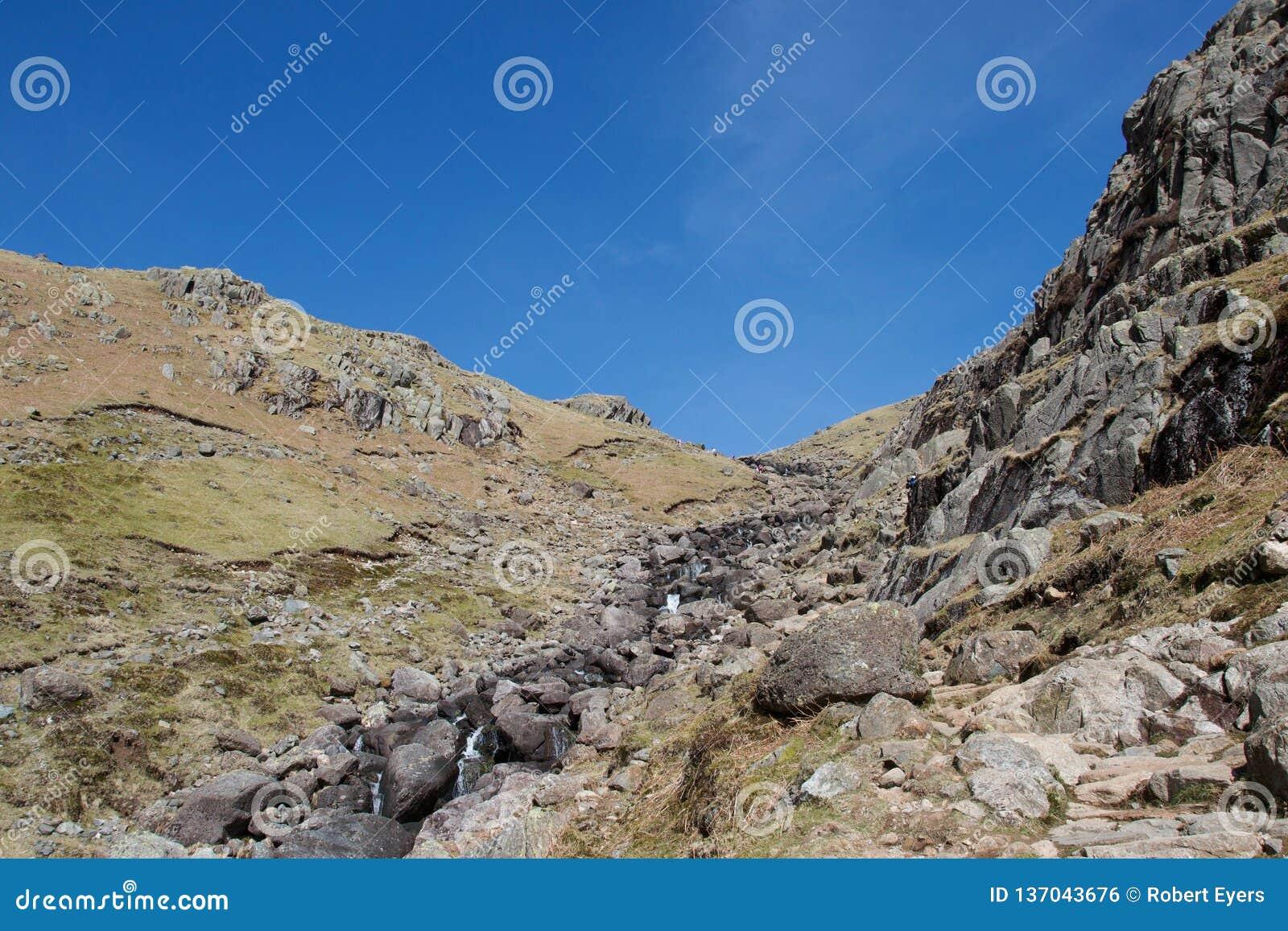 Torrente montano veloce che ruzzola fra le scogliere in un distretto del lago della valle, Regno Unito