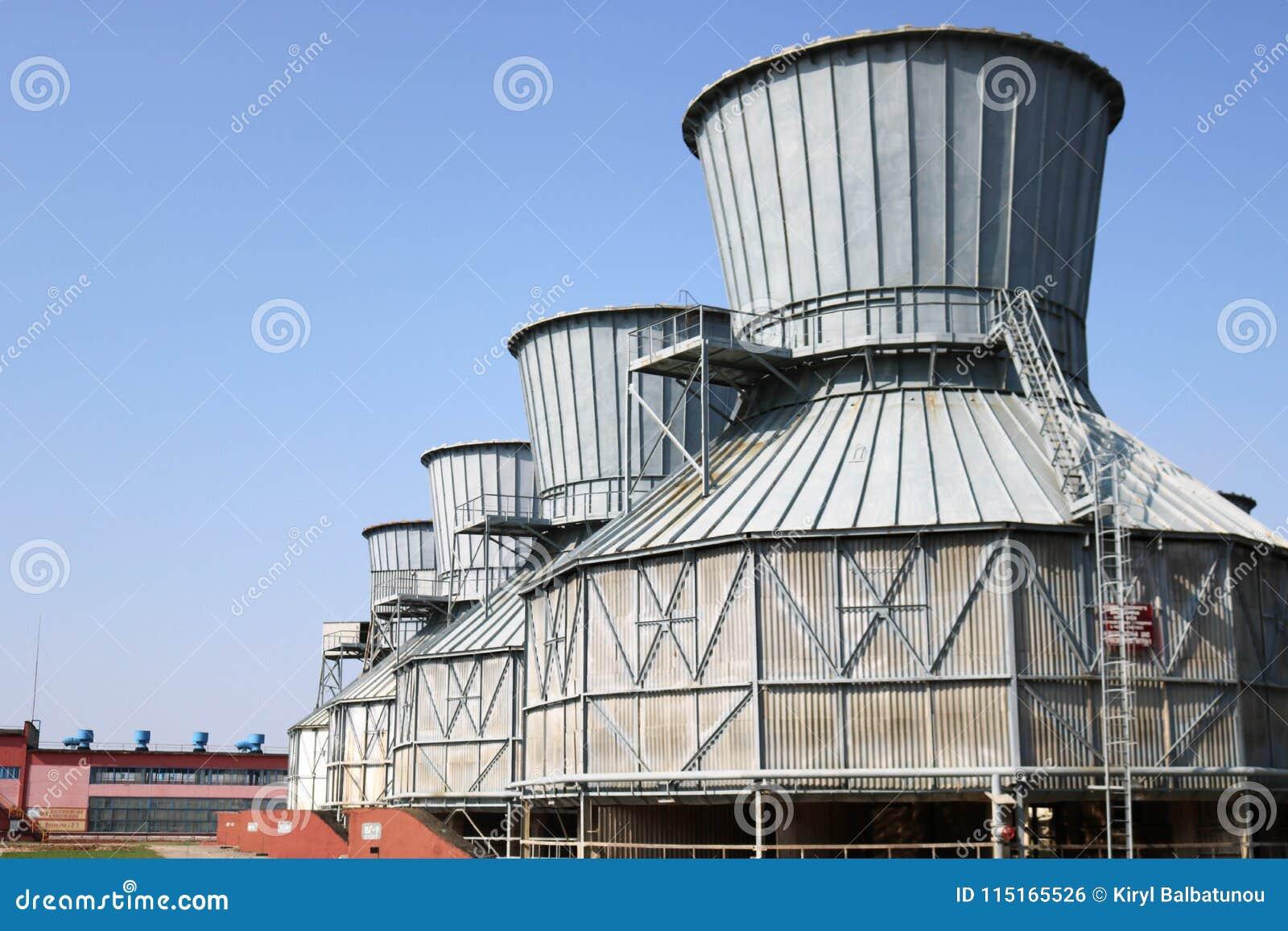 Torres de enfriamiento grises grandes para la agua en circulación de enfriamiento, colocándose en fila en una refinería de petról