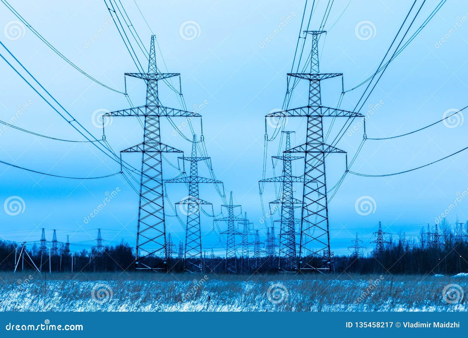 Torres de la tubería eléctrica en el campo del campo del invierno en el fondo del cielo azul y del bosque con los alambres