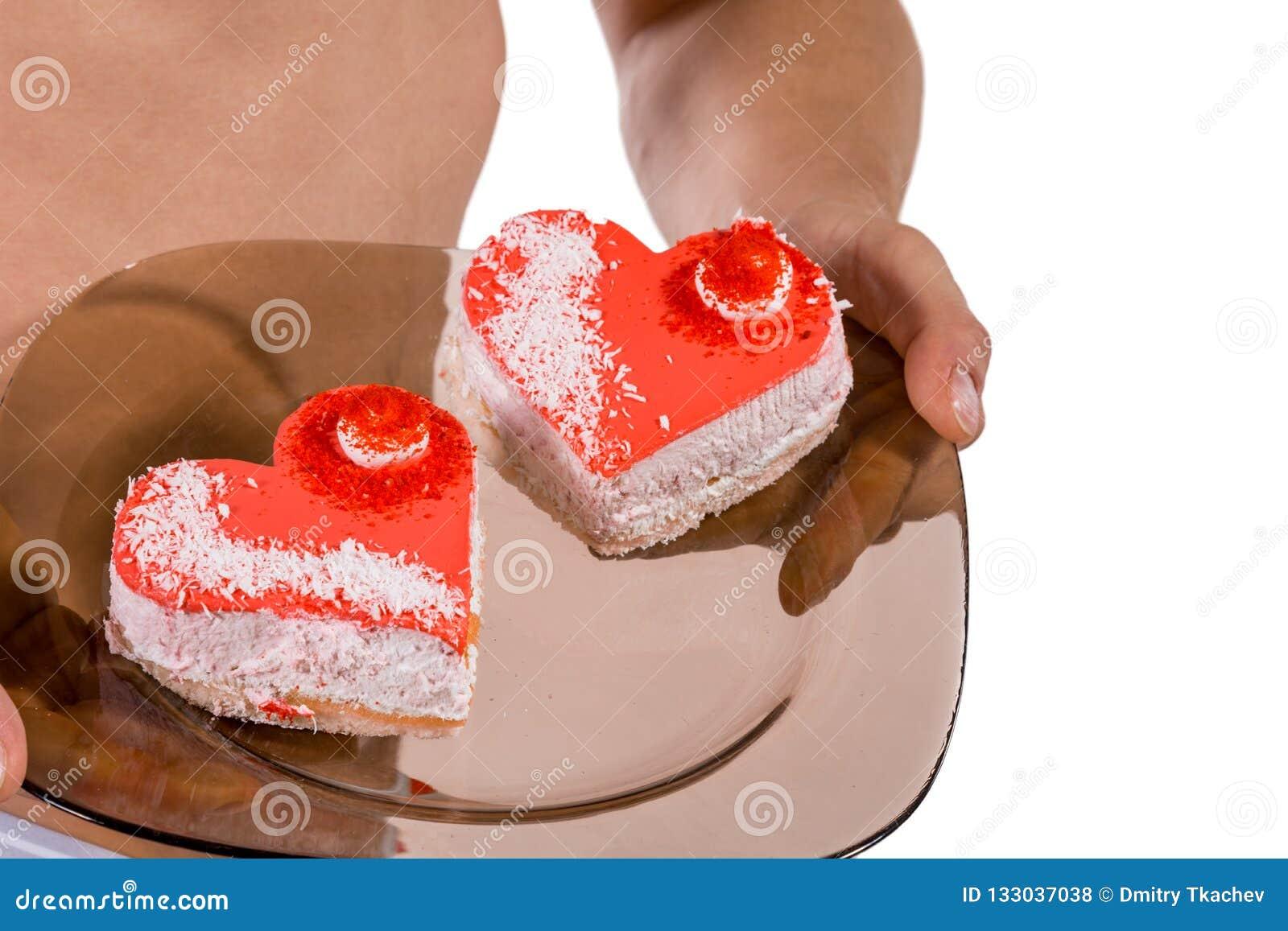 Torso van jonge knappe kerel met twee hart-vormige cakes op een plaat Sexy portret van de romantische mens met valentijnskaart