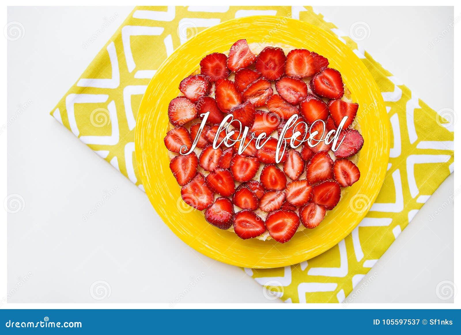 Torta brillante y deliciosa de la fresa en una servilleta amarilla, la comida del amor de la inscripción I