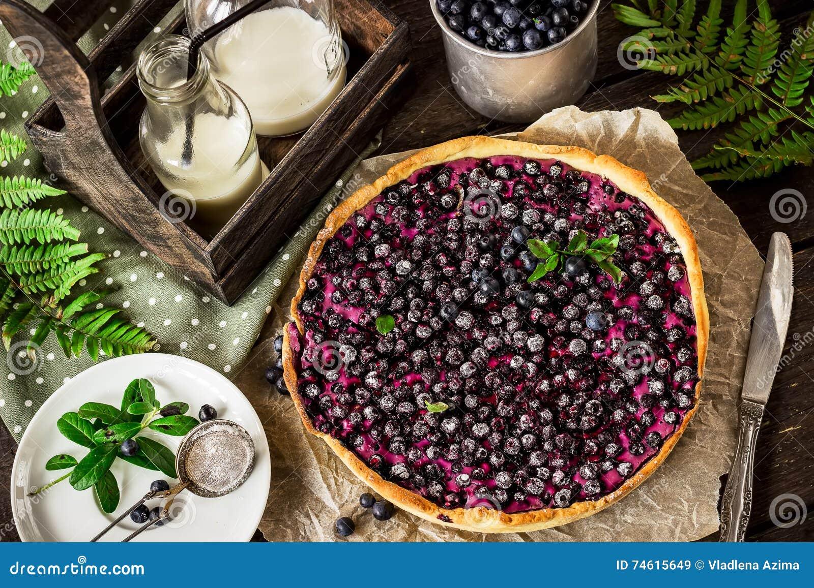Torta caseiro com uva-do-monte e leite na tabela de madeira escura