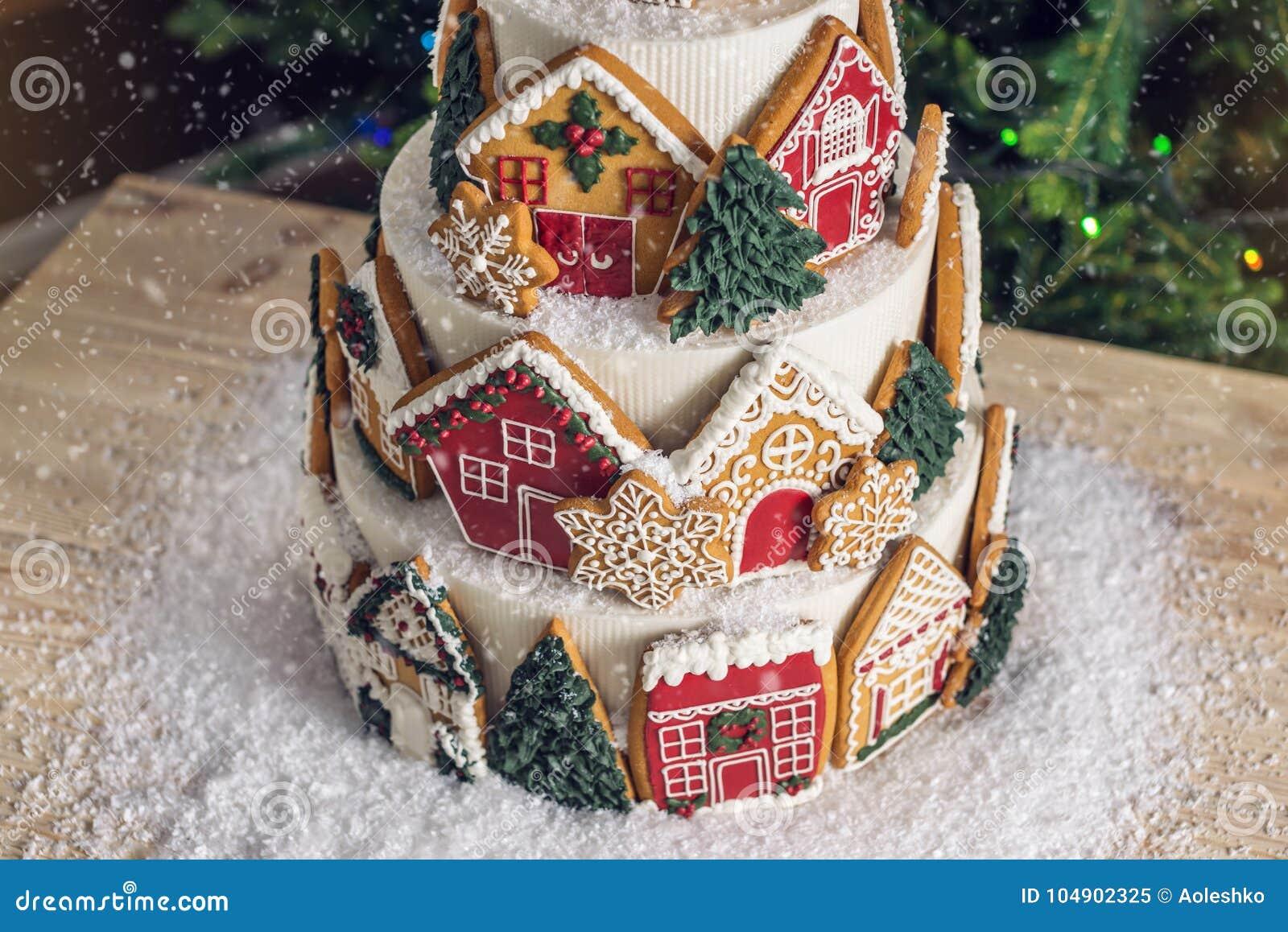 Torta con gradas grande de la Navidad adornada con las galletas del pan de jengibre y una casa en el top Árbol y guirnaldas en el