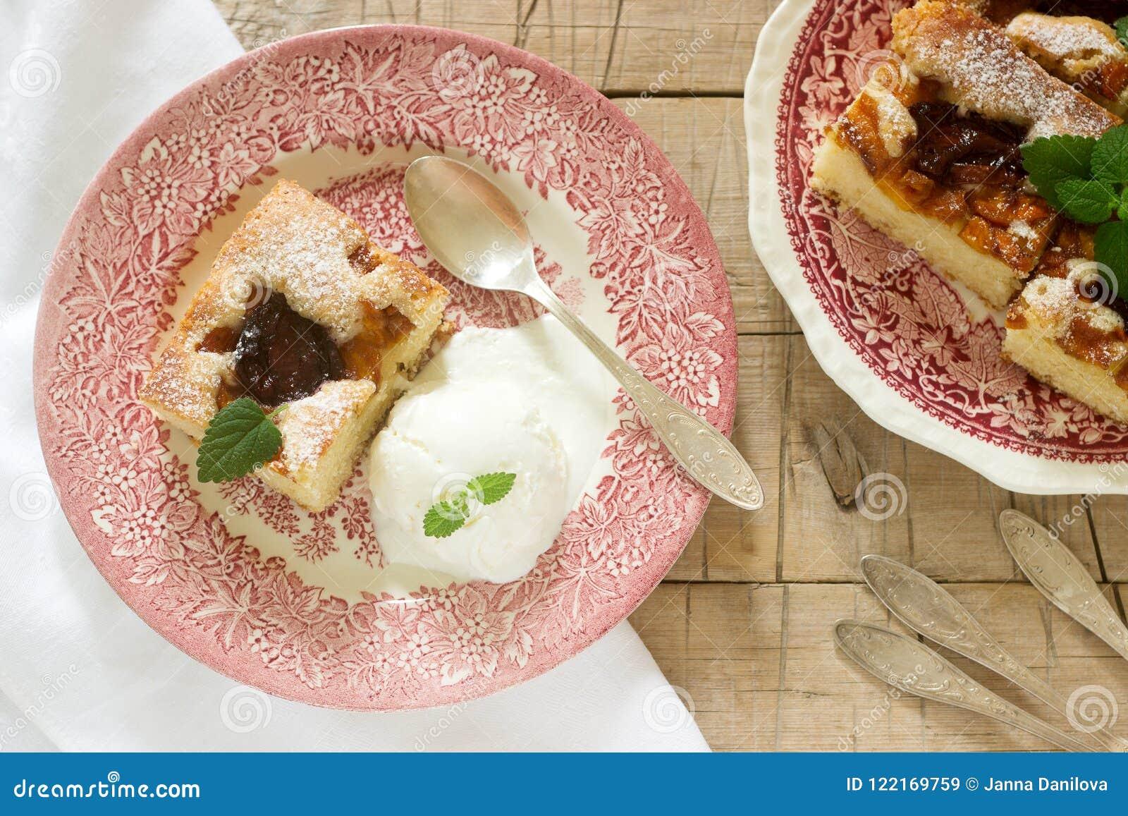 Torta con le prugne e le pesche, servite con una palla del gelato alla vaniglia e le foglie della melissa